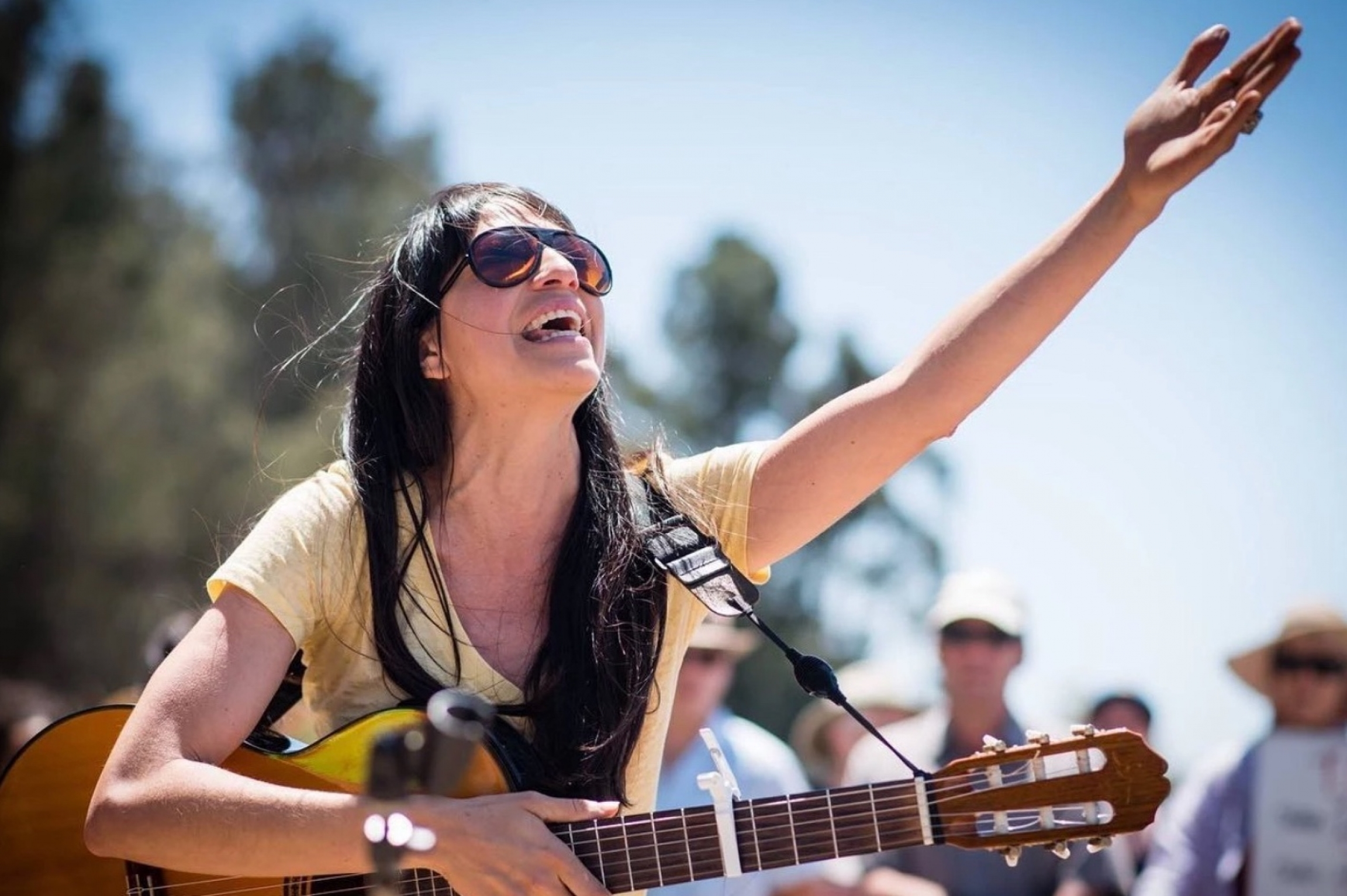 A woman wearing sunglasses holds a guitar in one hand while gesturing to the open blue sky with the other hand.