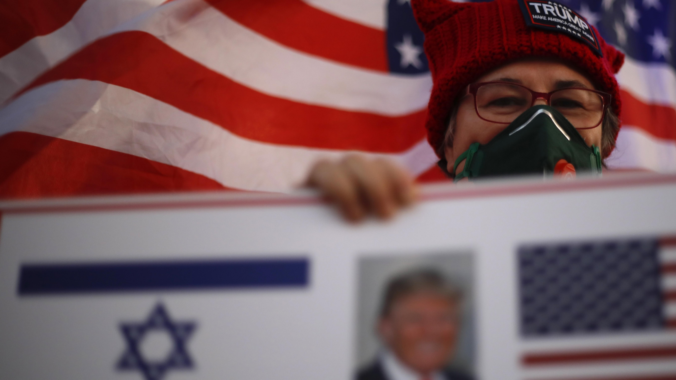 A supporter of US President Donald Trump waves Israeli and US national flags on the day of the U.S. presidential election, in Carmiel, northern Israel, Nov. 3, 2020.