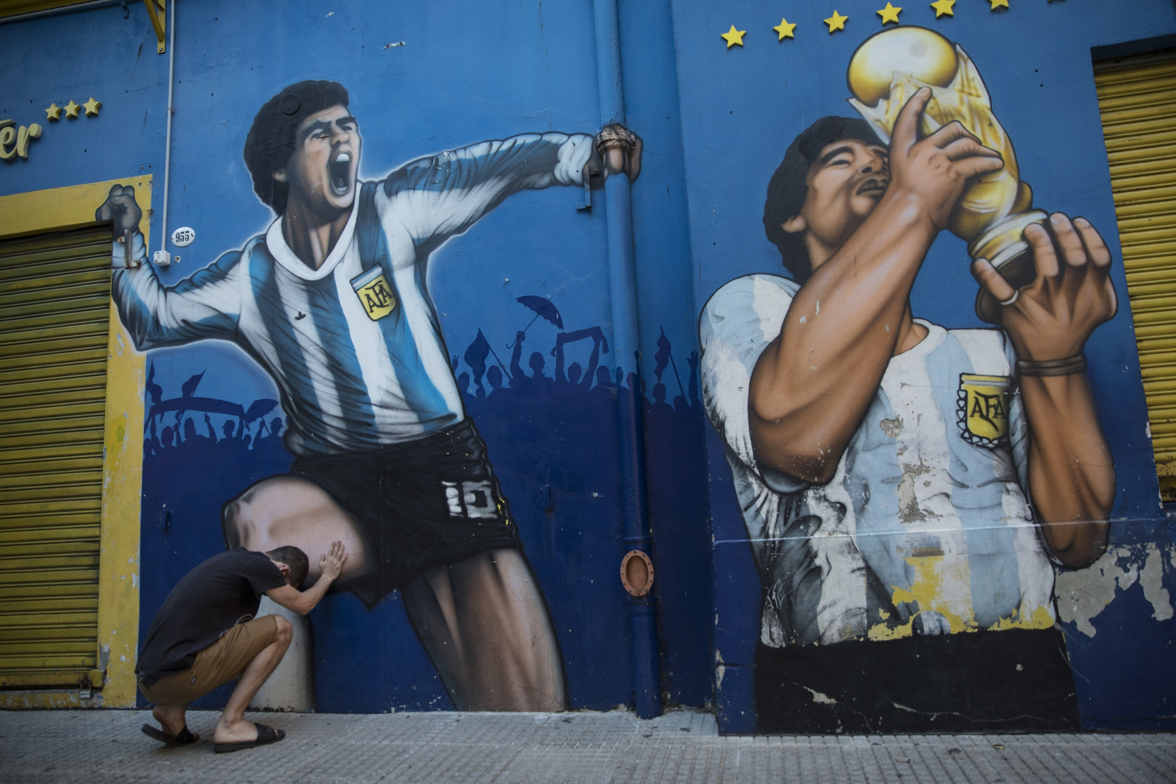 A man prays while touching a painting of Diego Maradona near the Boca Juniors stadium in Buenos Aires, Argentina, Nov. 27, 2020.