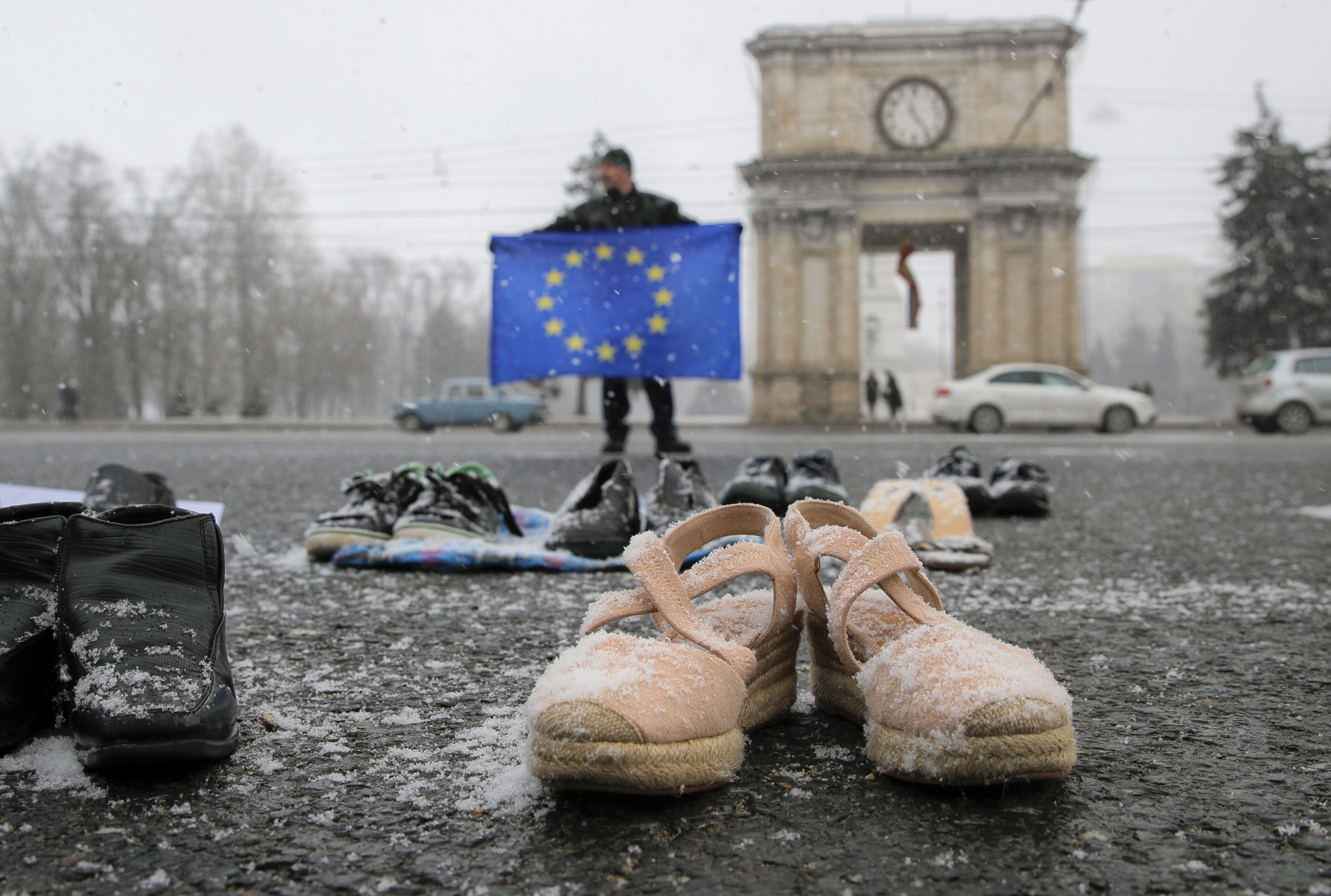A few pairs of shoes with snow on them lie in a square near a man with an EU flag with blue and yellow colors.