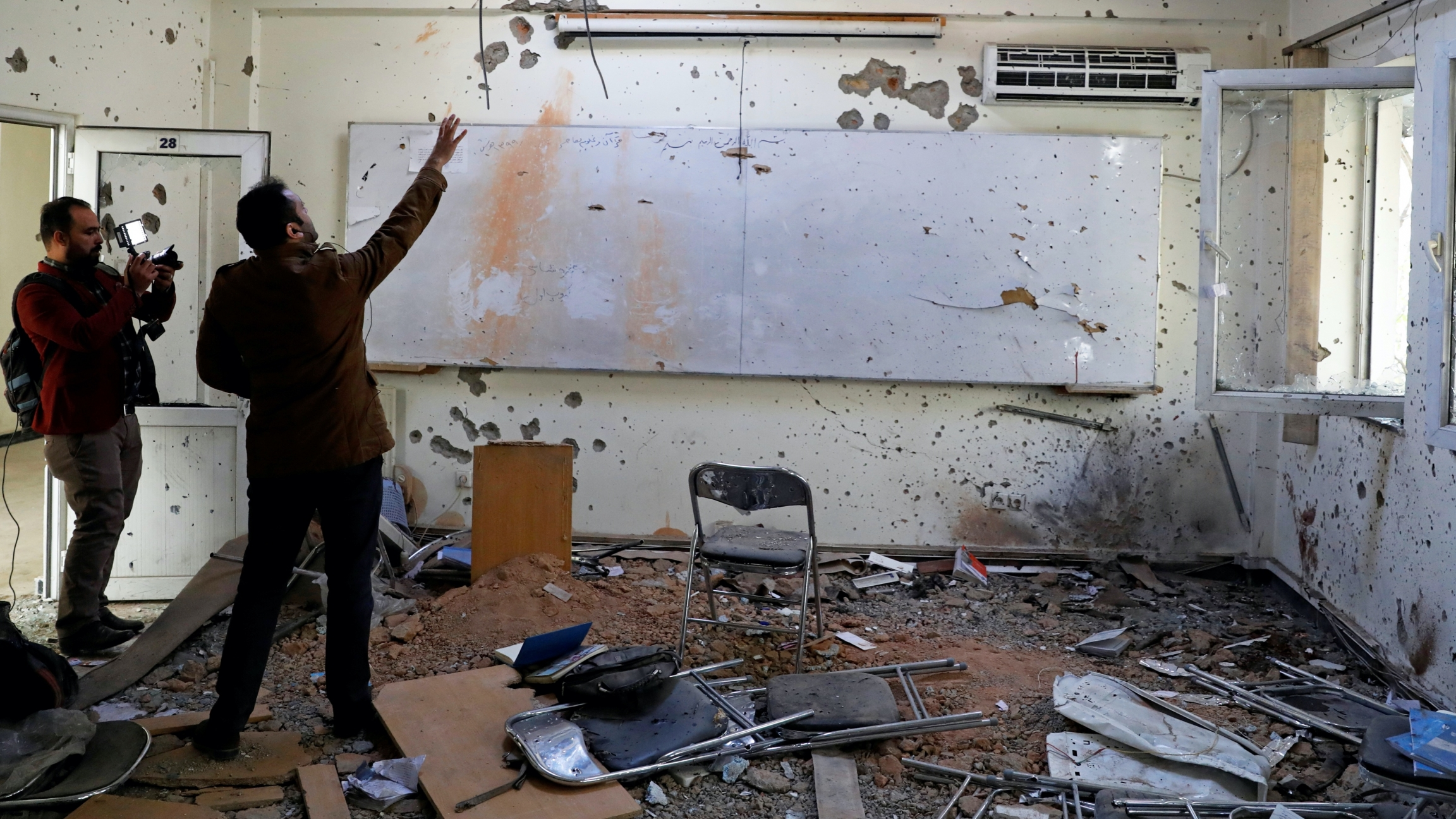 Two journalists look at a bombed out classroom with chair strewn and walls shot with bullets.