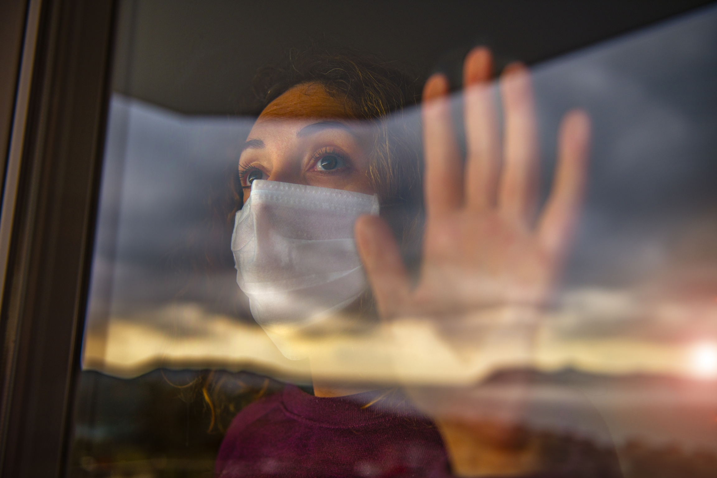 A woman with a mask looks out a window.