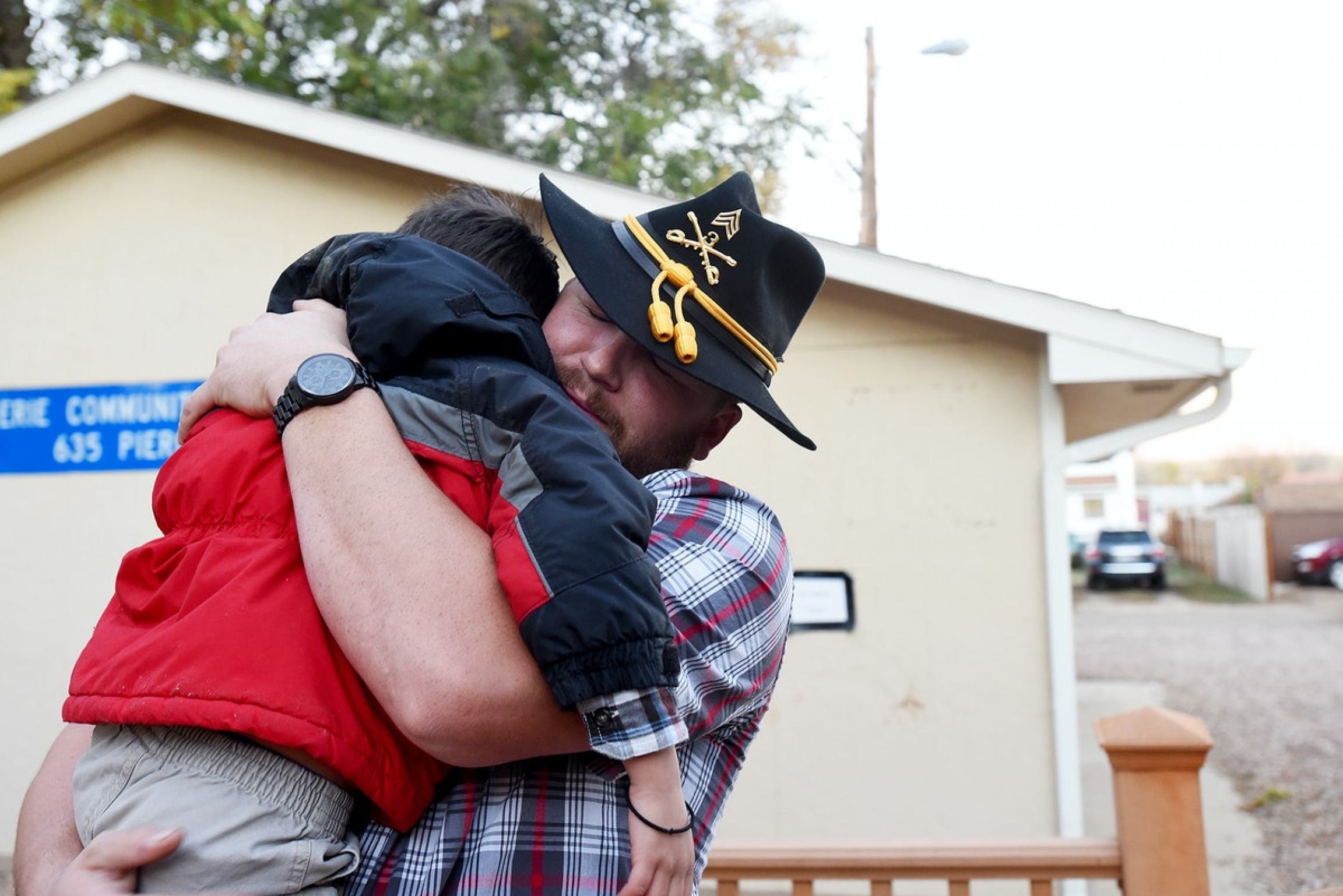 A veteran is hugged by his son