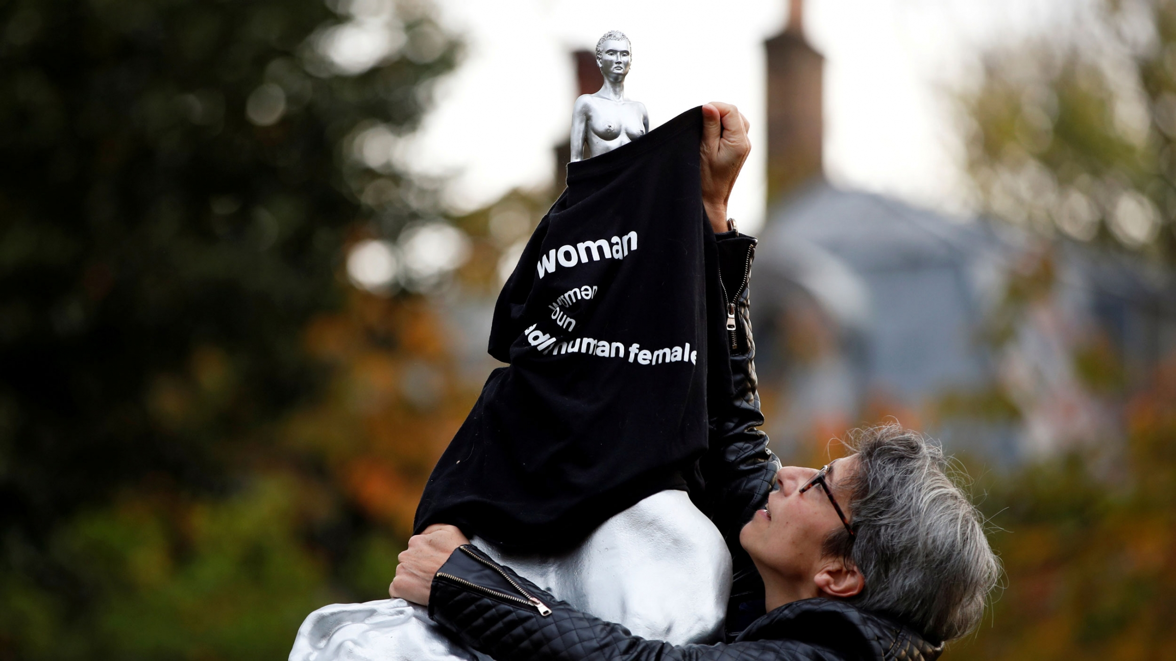 """A woman is shown covering a nude silver statue with a black T-shirt with the word, """"woman"""" printed on it."""