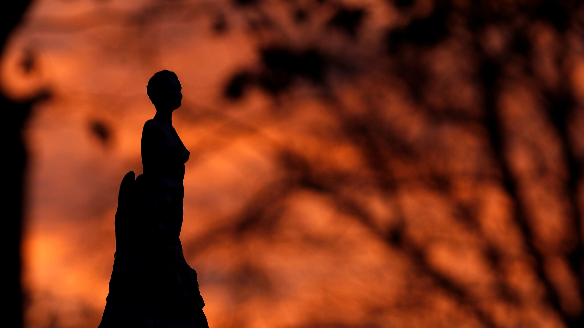 The dark silhouetted of a statue is shown with the orange and red colors of a sunset in the distance.
