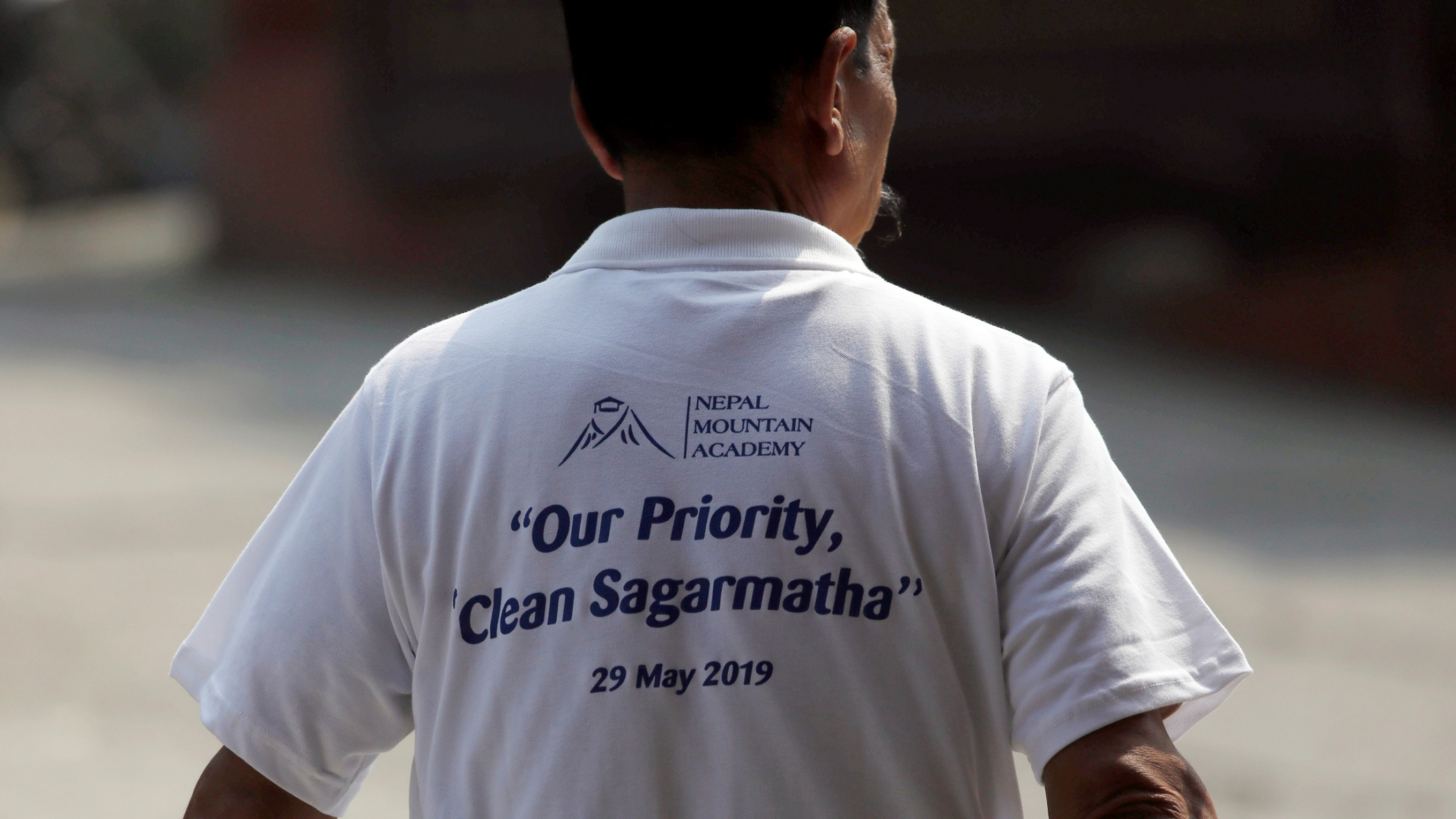 "A man wearing a t-shirt that reads ""Our Priority, Clean Sagarmatha"" during the anniversary of Edmund Hillary and Tenzing Norgay Sherpa's assent of Mount Everest in 1953, as well as to mark International Everest Day in Kathmandu, Nepal. May 29, 2019."