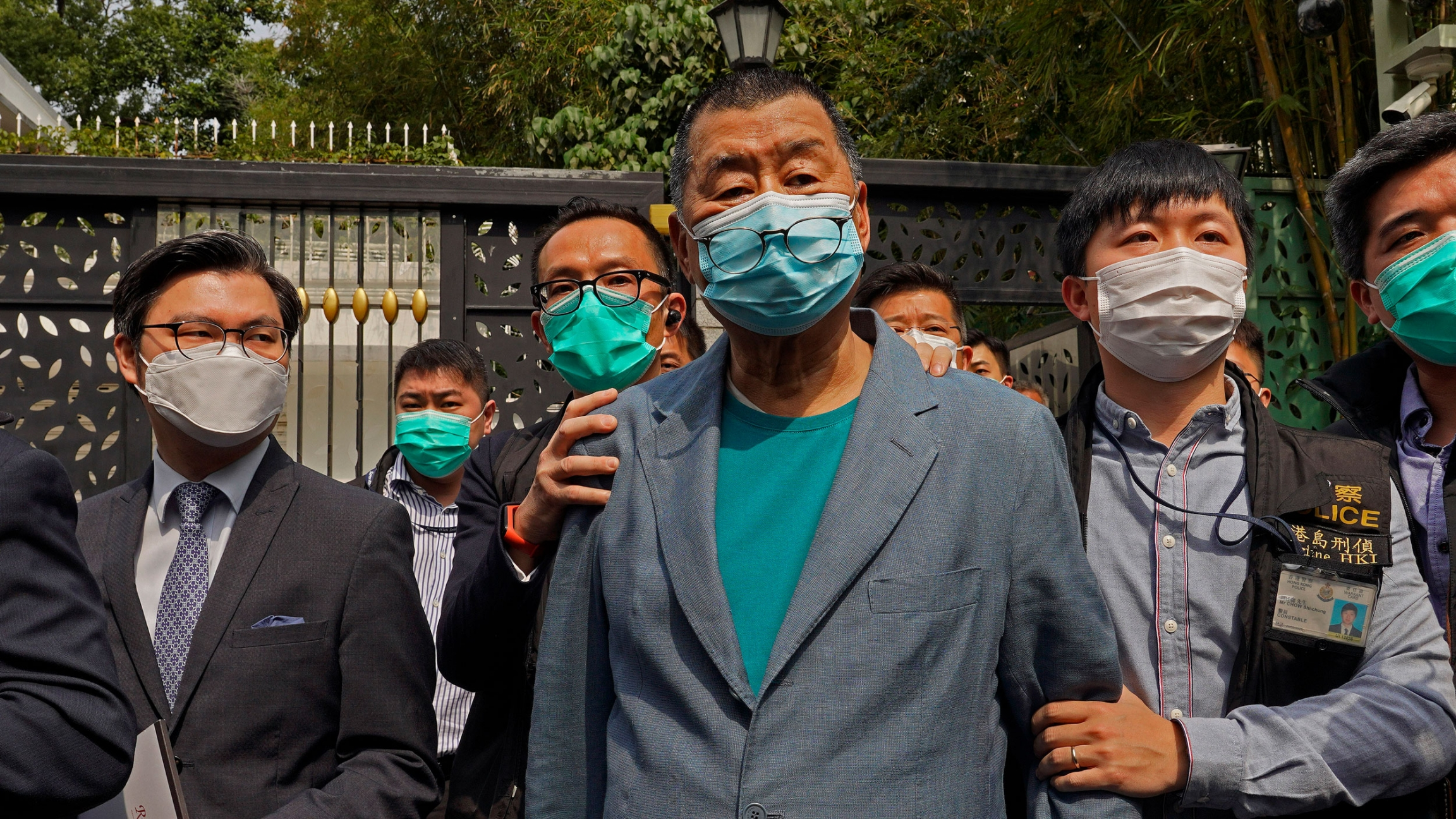 Jimmy Lai is shown being held by security officials while wearing a blue blazer and a face mask.
