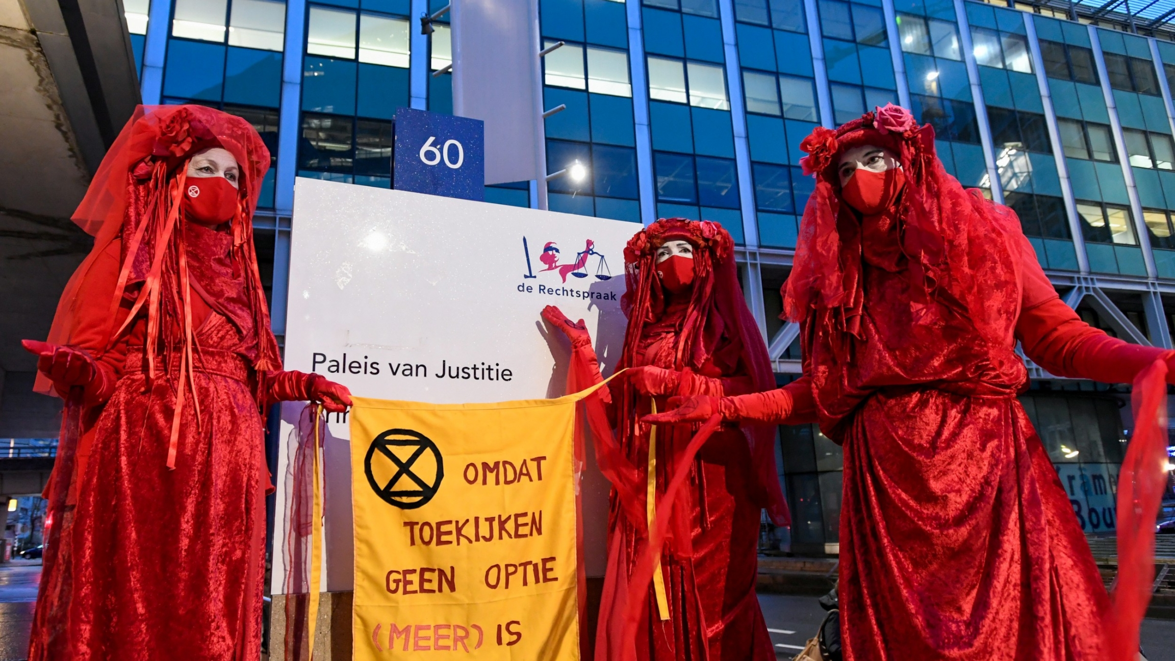 "Environmental activists hold a banner that reads: ""Because watching is not an option [anymore],"" as they protest outside of a court during a hearing in a case environmentalist and human rights groups have brought against Royal Dutch Shell to force the ene"
