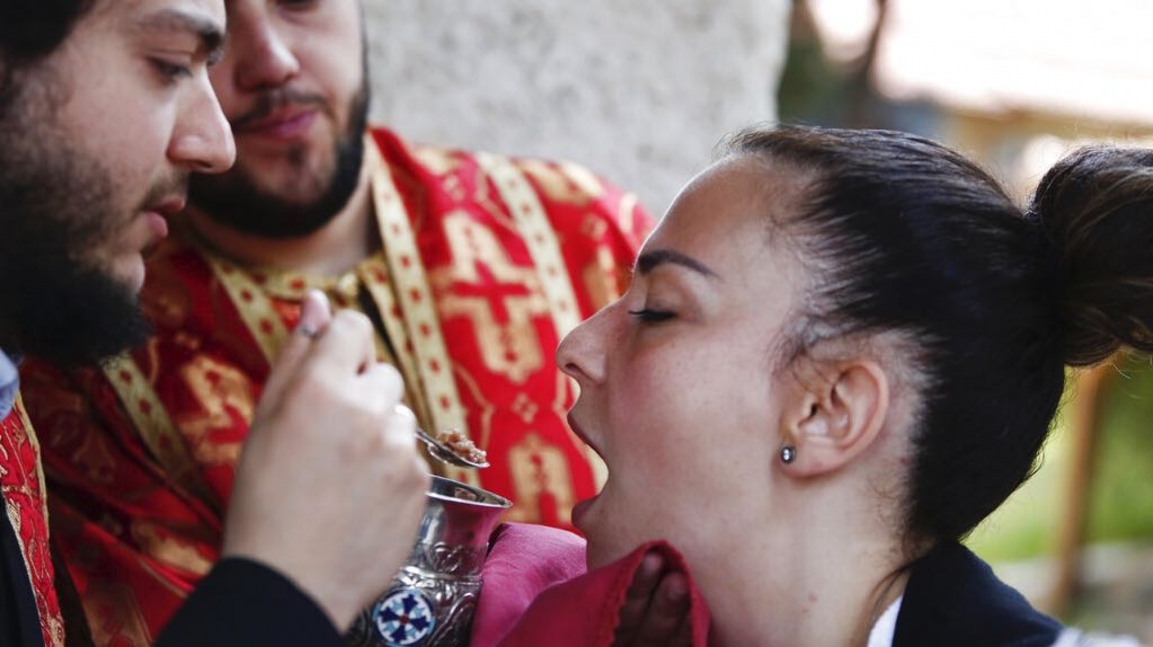 In this Sunday, May 24, 2020, photo, a Greek Orthodox priest distributes Holy Communion during Sunday Mass at a church, in the northern city of Thessaloniki, Greece, using a traditional shared spoon. Contrary to science, the Greek Orthodox Church insists