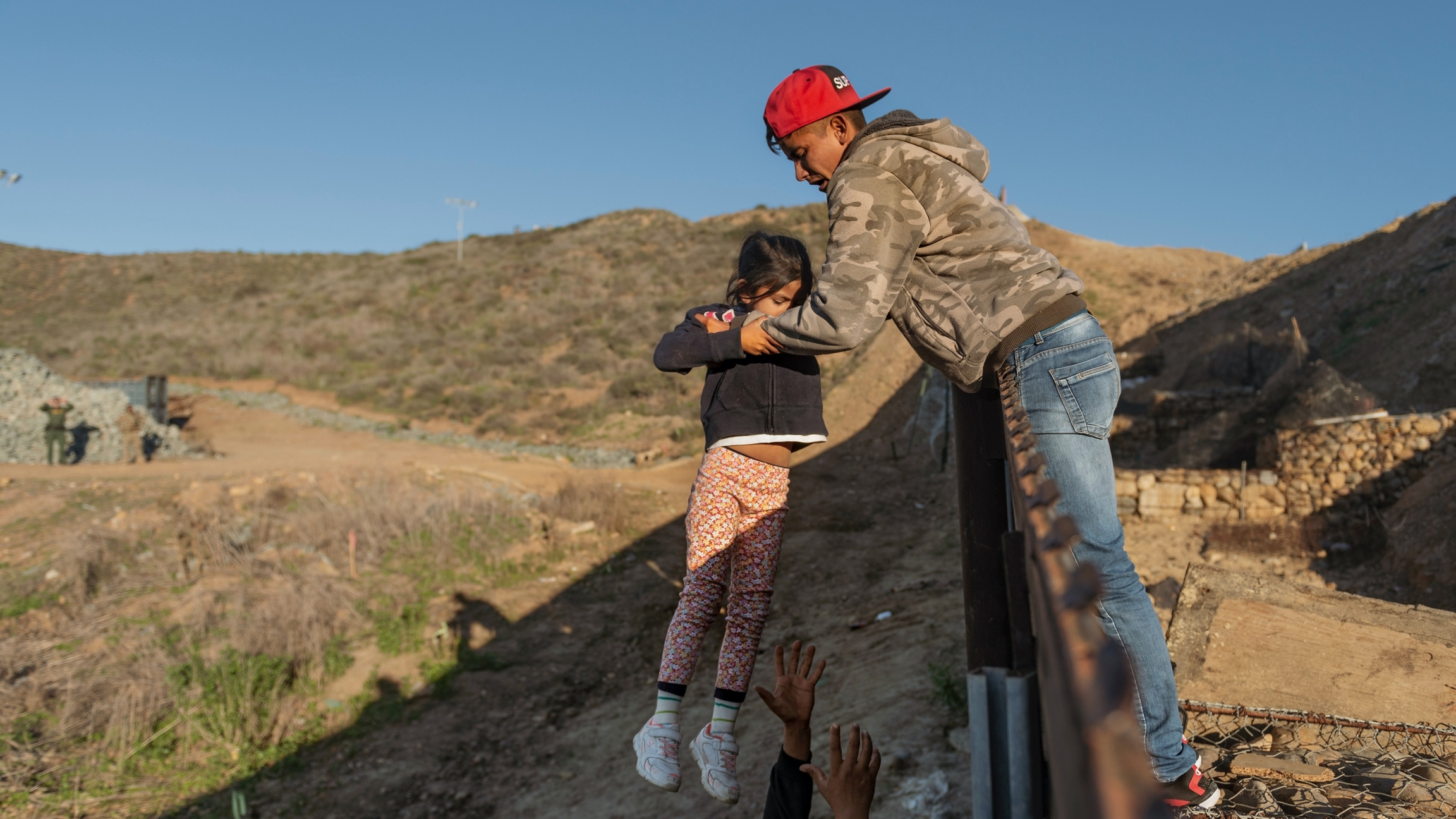 A child is passed over a border wall to the arms of a man wearing jeans, a red cap and tan sweatshirt.