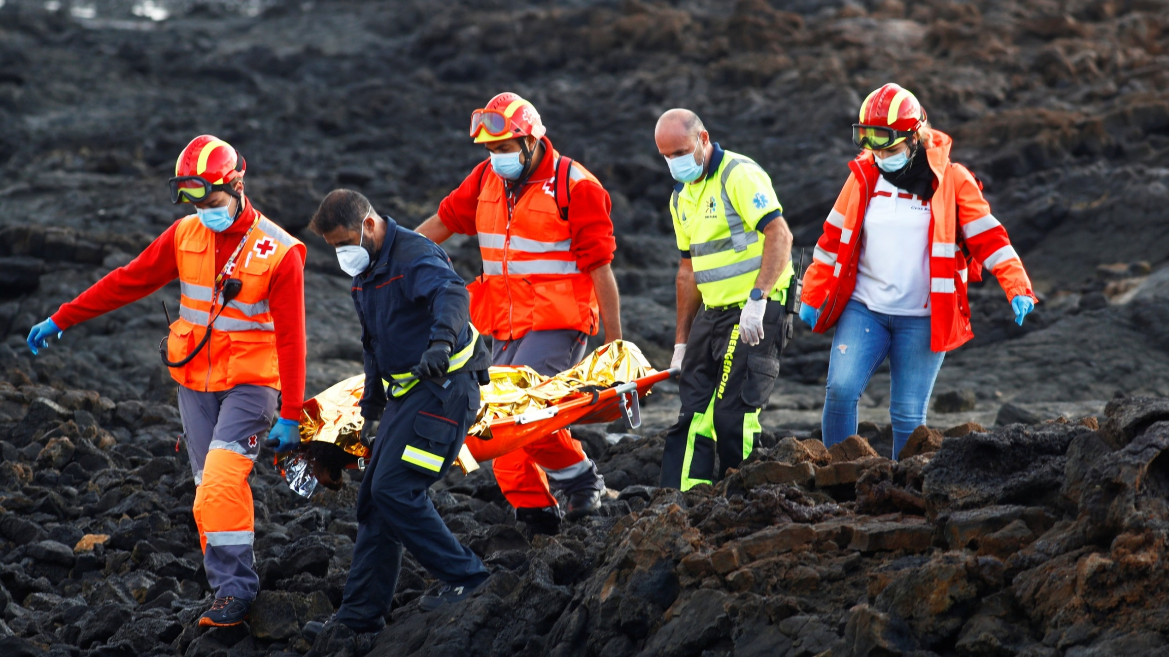 Rescue workers carry the body of a dead migrant after a boat with 35 migrants from the Maghreb region capsized at the beach of Orzola, in the Canary Island of Lanzarote, Spain, Nov. 25, 2020.
