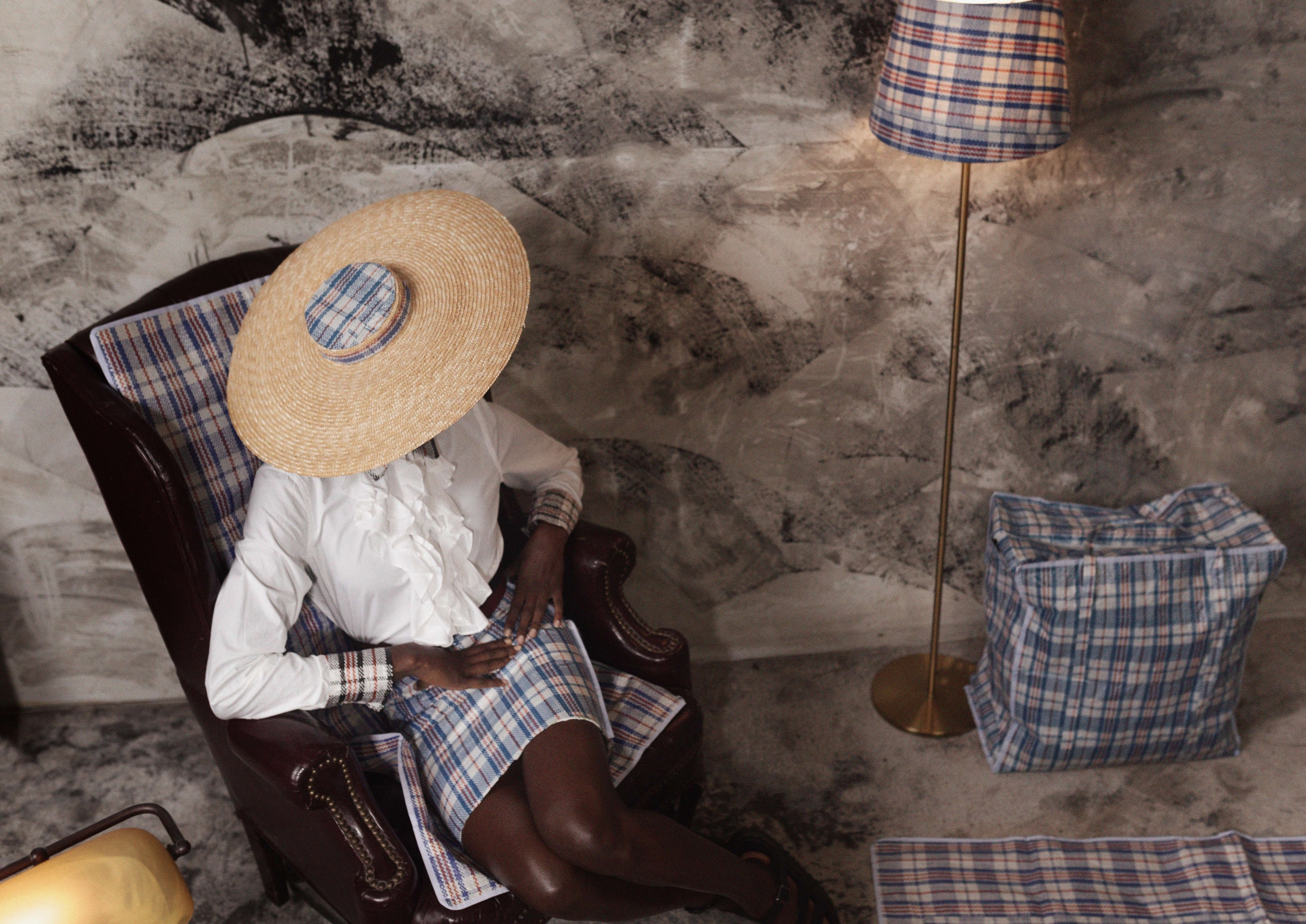 A woman sits wearing a hat, white blouse and plaid plastic skirt with lamp shade of same fabric near plaid travel bag