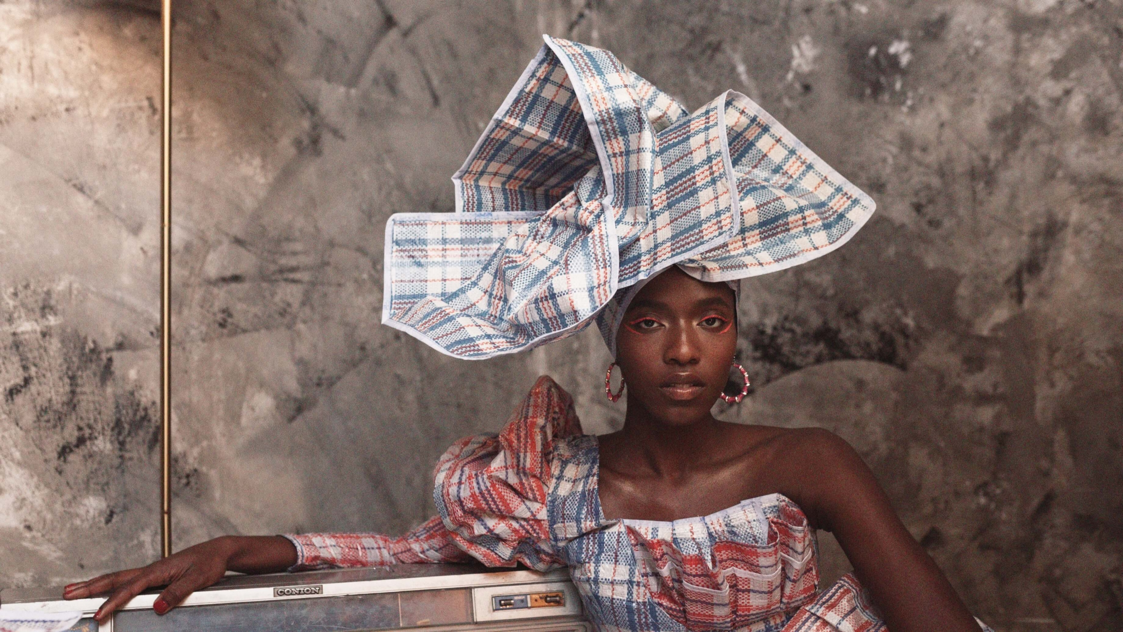 A woman wears a plaid head wrap and dress and poses near a transistor radio