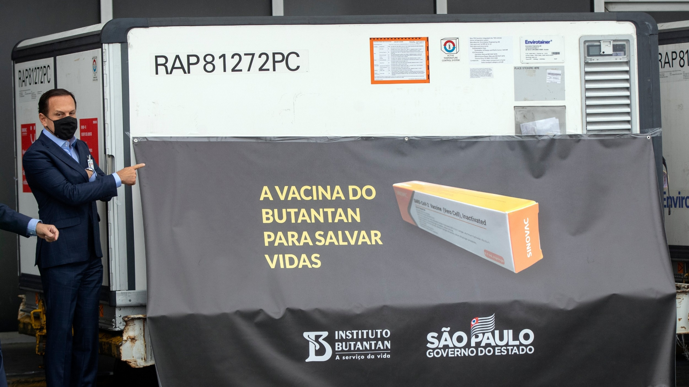 São Paulo Governor João Doria points to a container carrying the experimental COVID-19 vaccine CoronaVac during a photo opportunity, after it was unloaded from a cargo plane that arrived from China at Guarulhos International Airport near São Paulo, Brazil