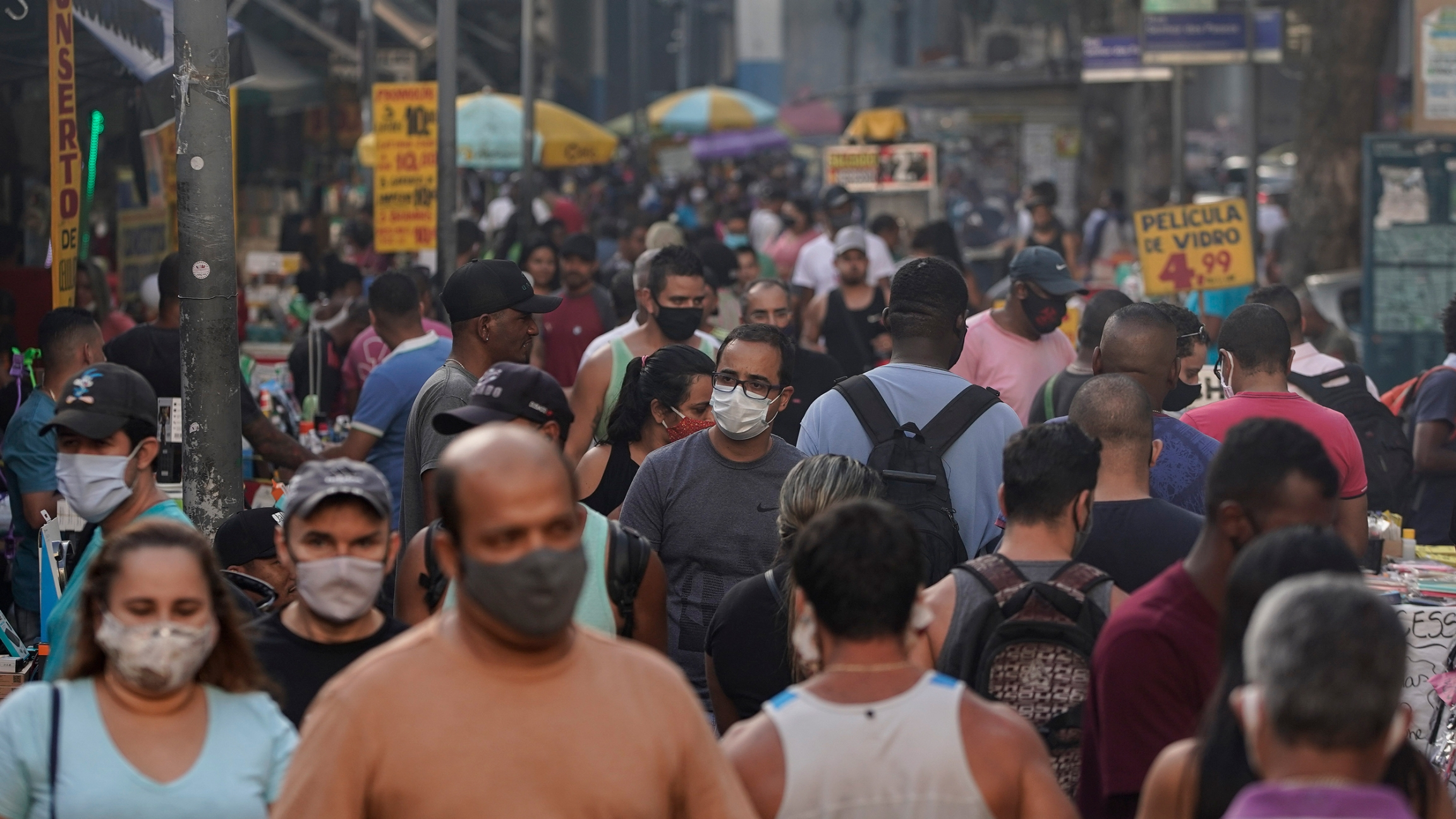 A crowded street is shown with some people wearing face masks.