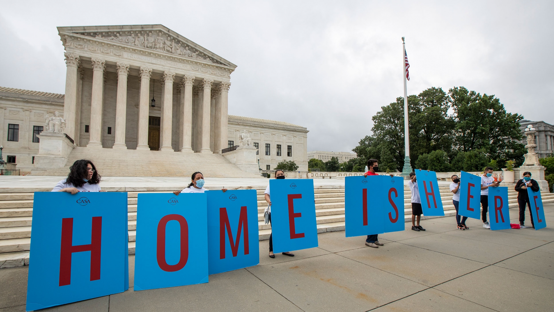 """Several people are shown standing behind large placards that together spell out, """"Home is here."""""""