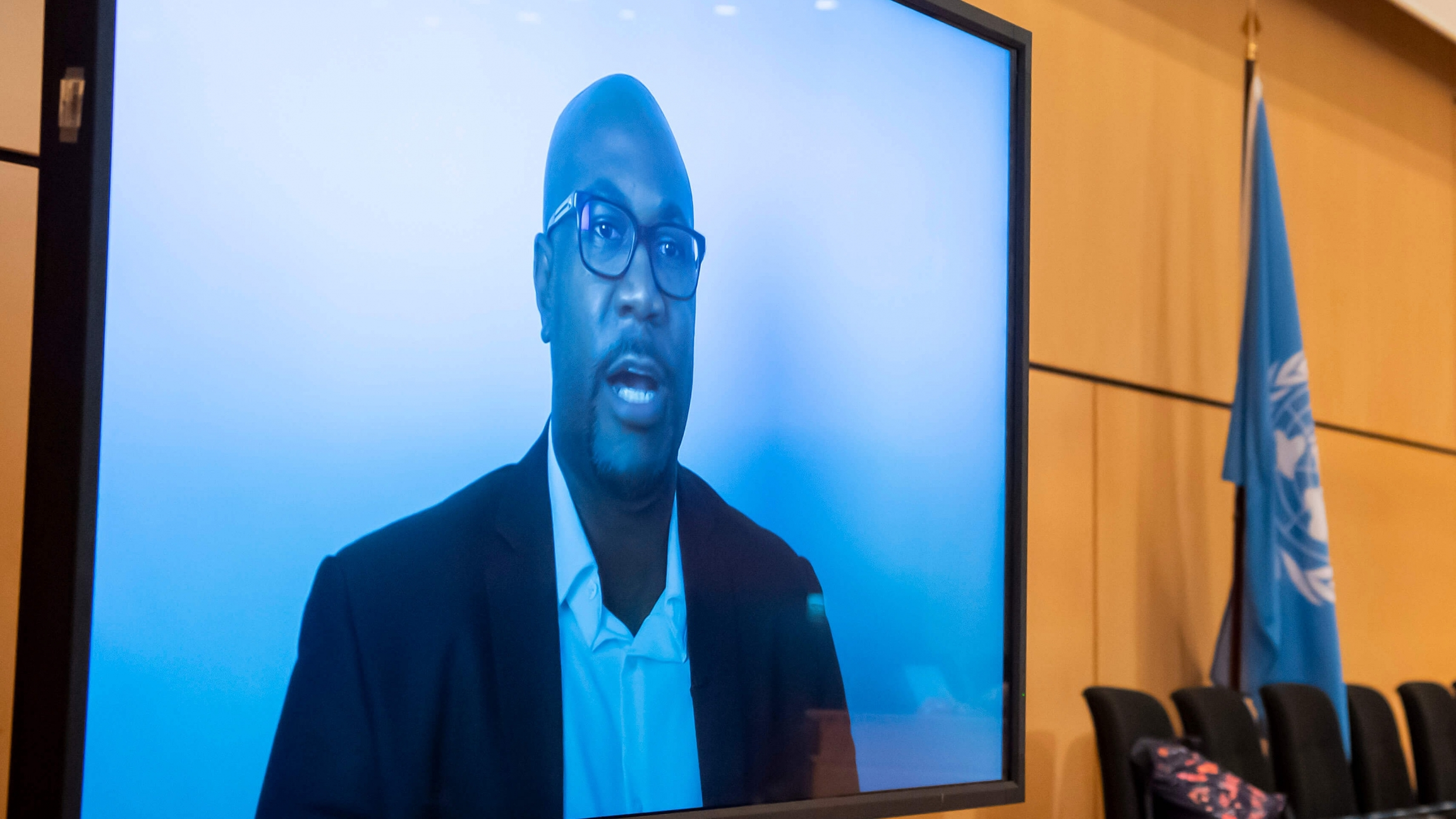 A Black American man wears glasses and a blue suit jacket and speaks via video with a blue background