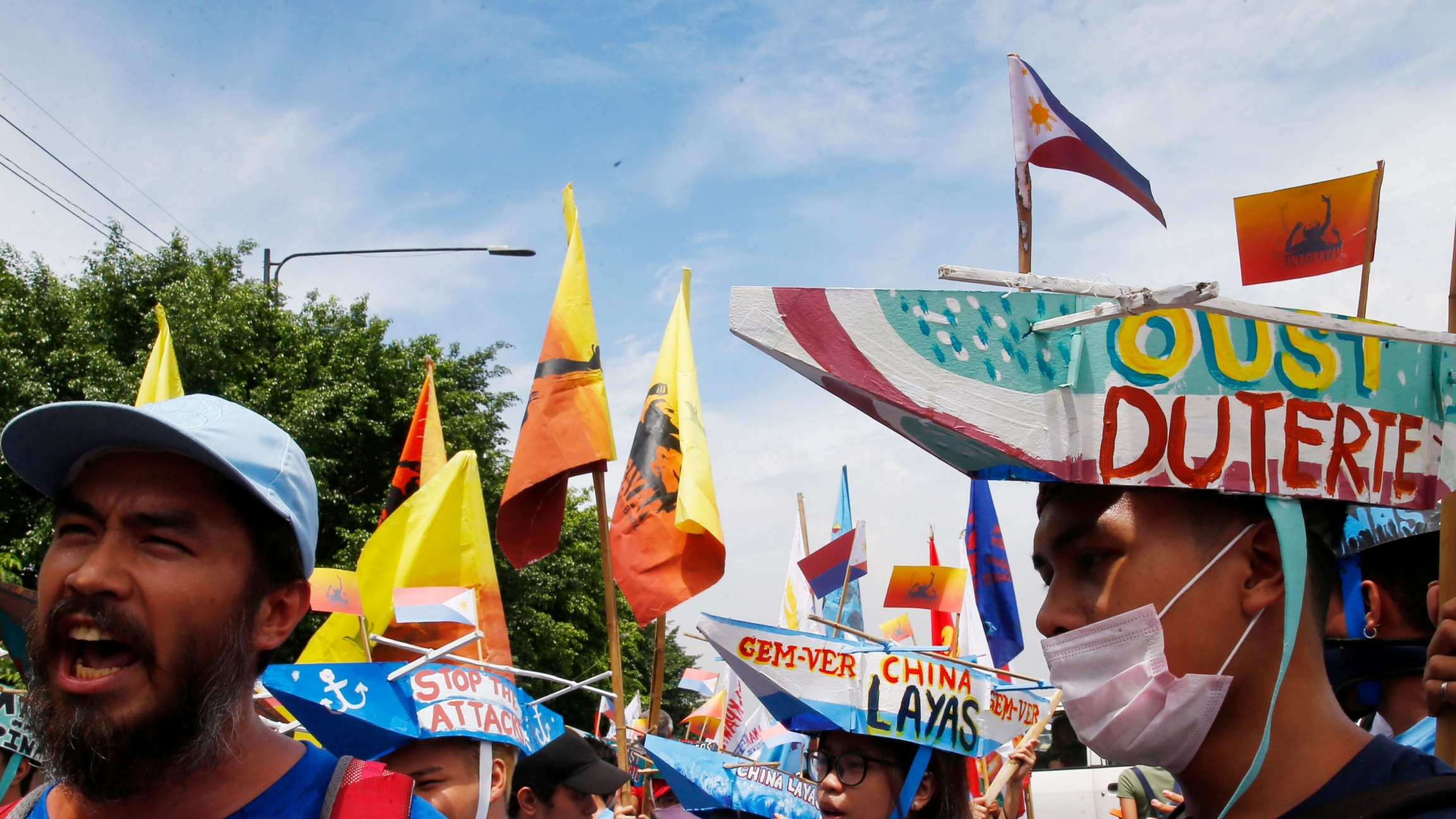 """Protesters shout and wear a colorful boat on their heads with the words """"oust Duterte"""" painted on it."""