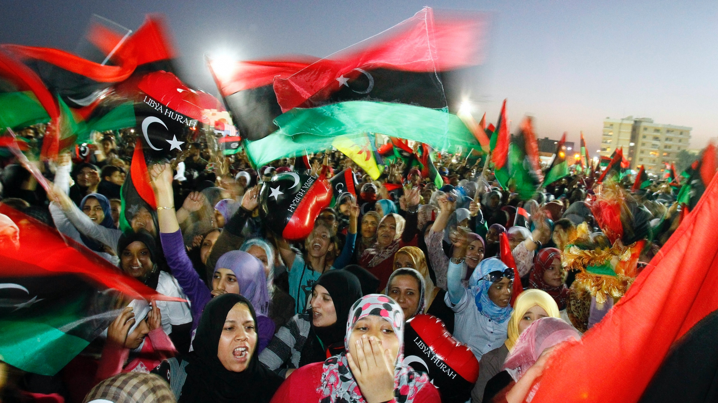 A crowd of people celebrate with flashes of red, black and green flags waving in the air.