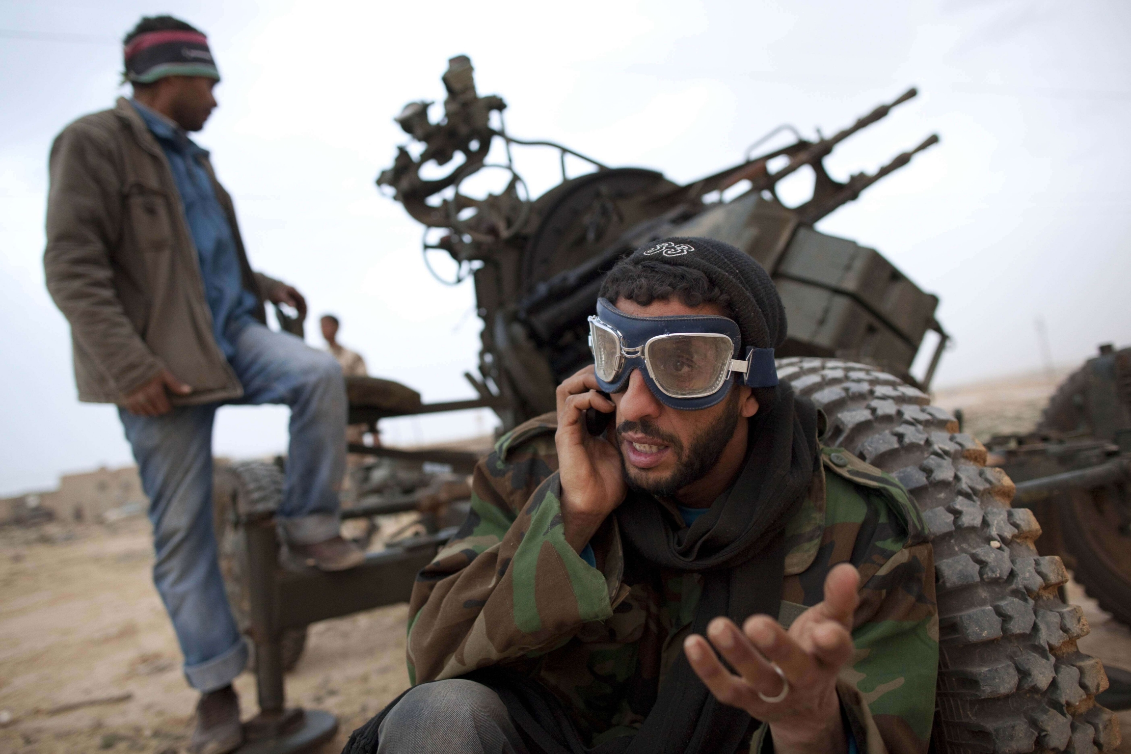 In this March 4, 2011 file photo, Libyan rebels who are part of the forces against Libyan leader Moammar Gadhafi stand with an anti-aircraft gun as they prepare to fight on the front-line near Ras Lanuf, west of the town of Brega, eastern Libya.