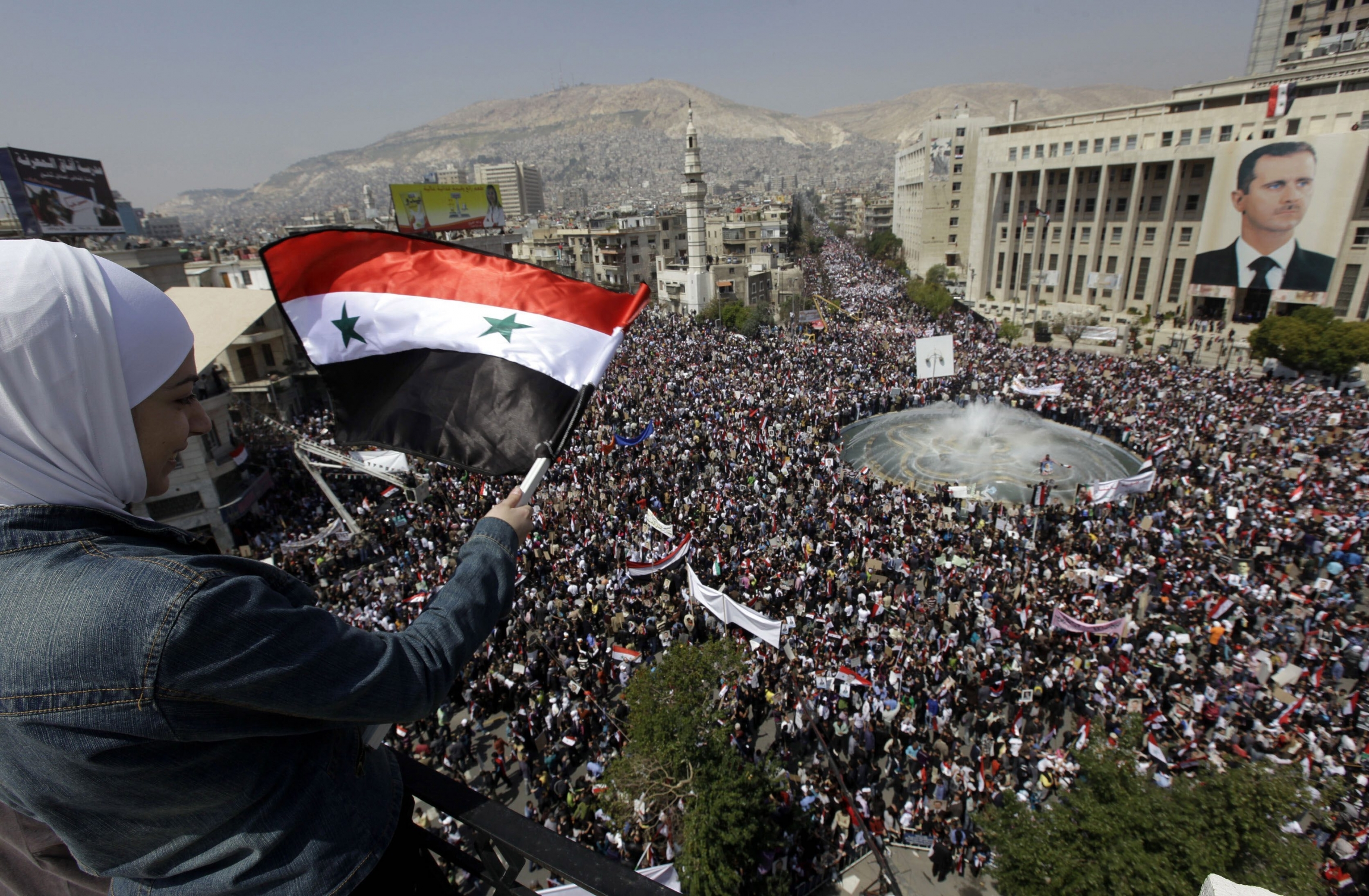 A supporter of Syrian President Bashar Assad waves a Syrian flag as she looks over a crowd gathered to show support for their president in Damascus, Syria, March 29, 2011.