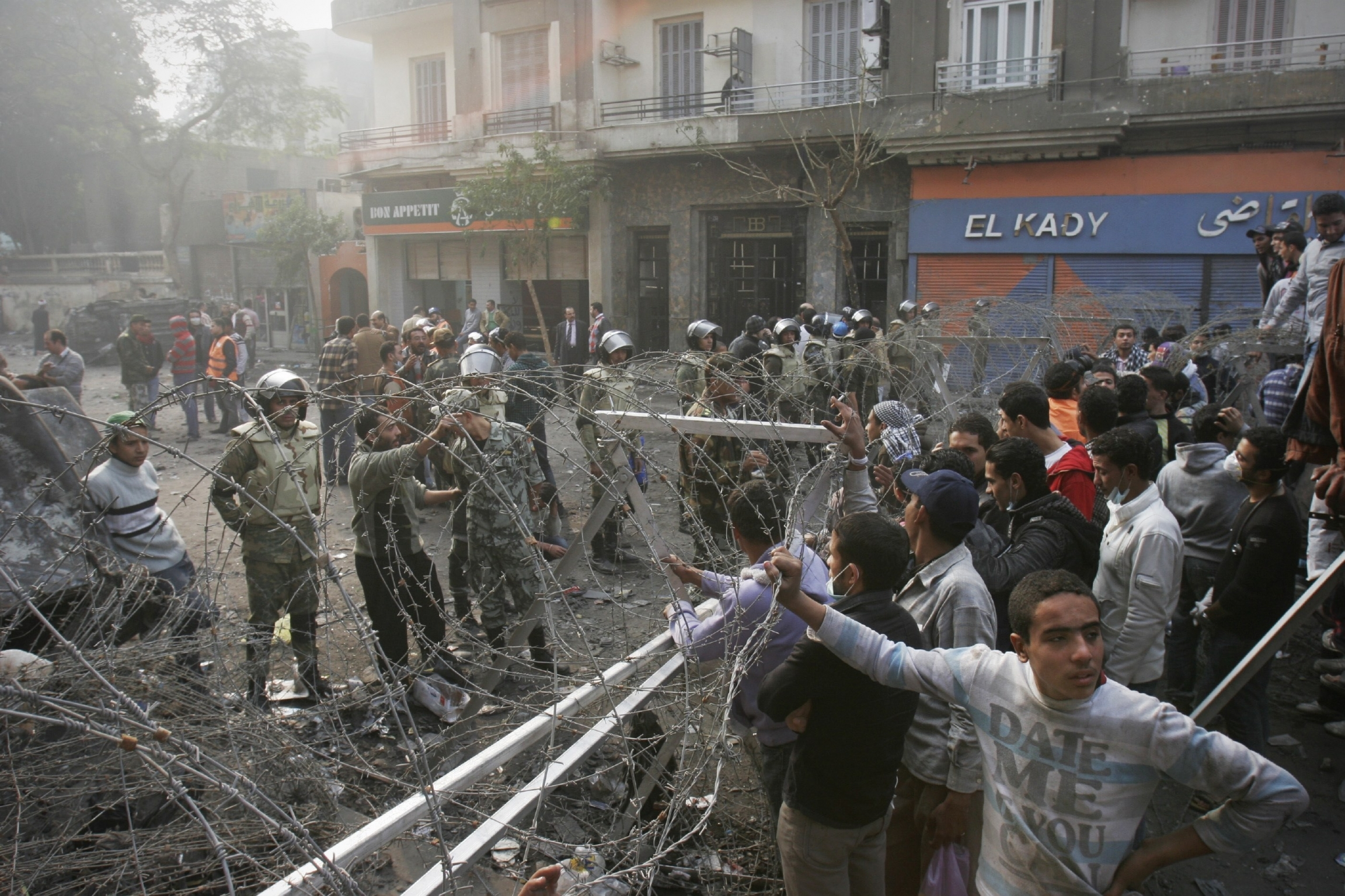 In this Thursday, Nov. 24, 2011 file photo, Egyptian protesters stand behind a barbed wire barricade in Tahrir Square in Cairo, Egypt.