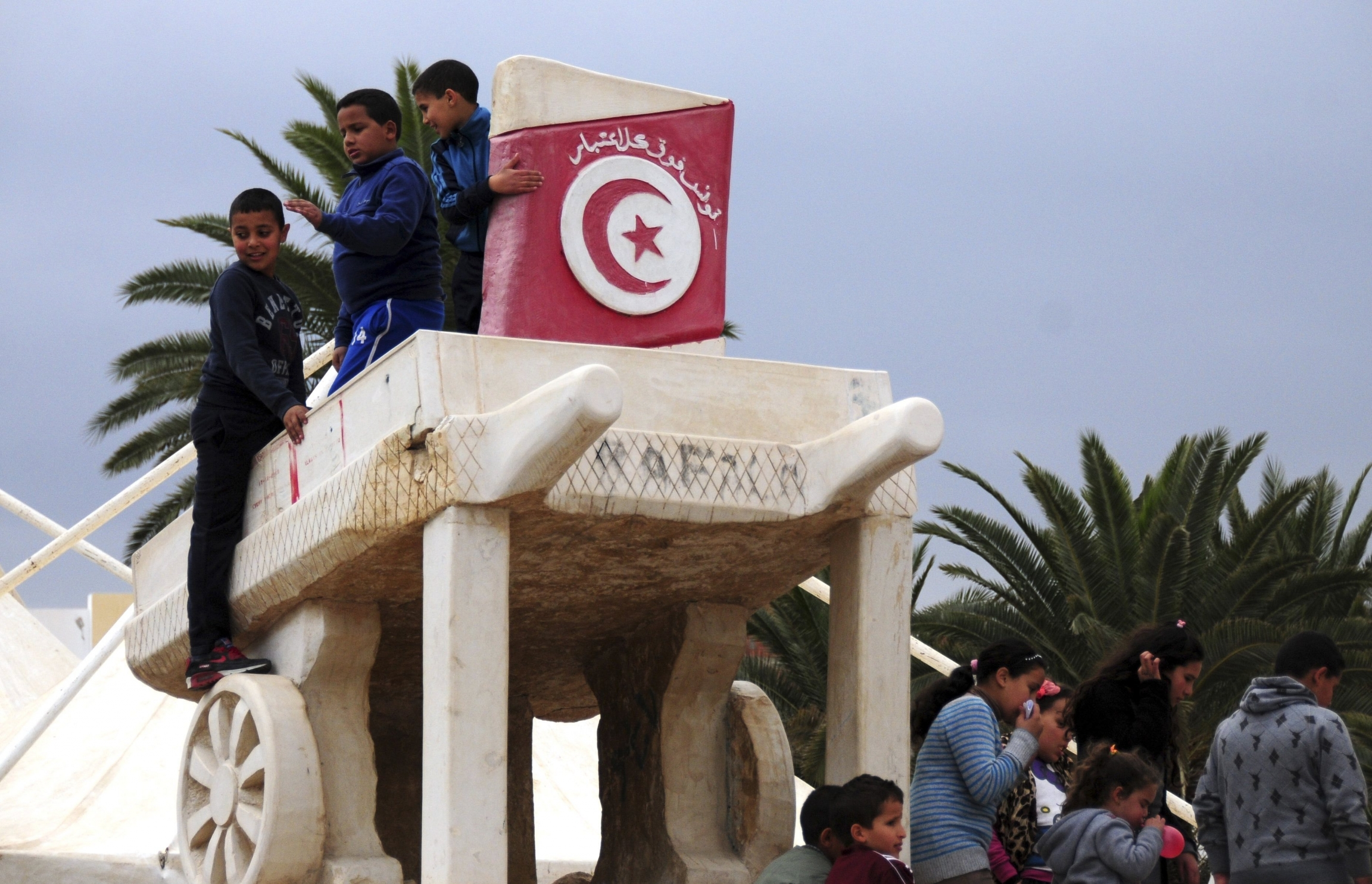 Children play on a statue of a wooden cart like that used by Mohamed Bouazizi to sell fruits, in Sidi Bouzid, Tunisia, Dec.17, 2015. Tunisians who won the Nobel Peace Prize joined townspeople in the country's beleaguered heartland to mark five years since