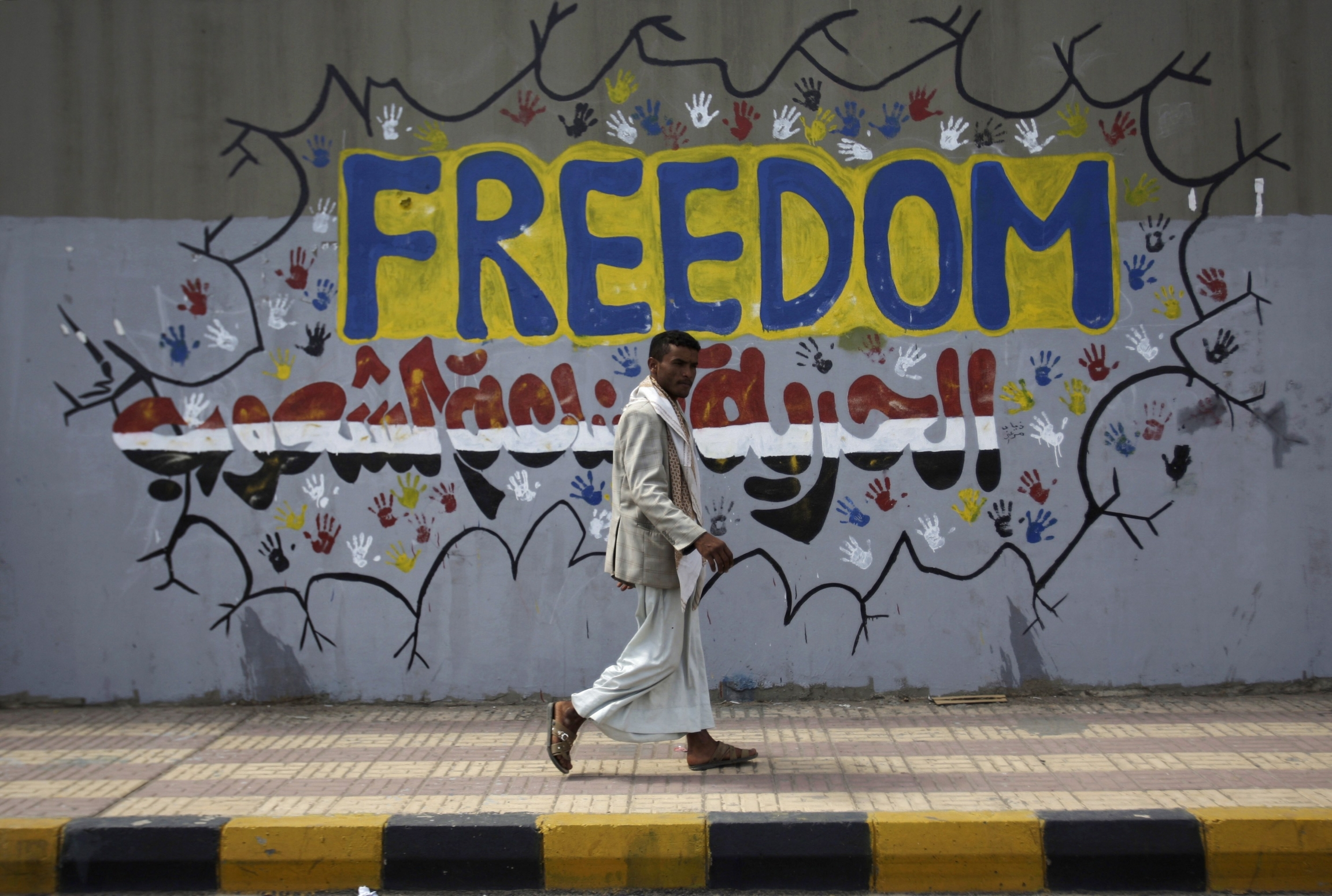 "In this Friday, March 2, 2012 file photo, a Yemeni walks past a graffiti that reads ""Freedom is made by people"" on a street where protesters demanded a trial for the former President Ali Abdullah Saleh, in Sanaa, Yemen."