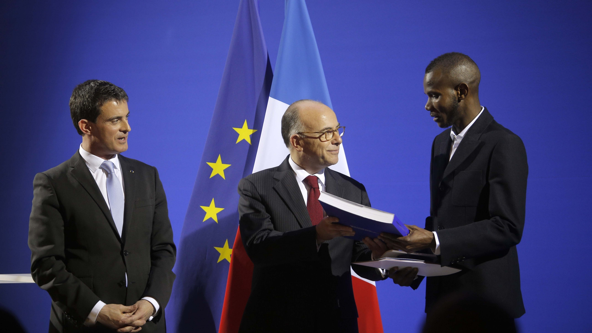 French Prime Minister Manuel Valls, left, and French Interior Minister Bernard Cazeneuve, center, award citizenship to Lassana Bathily during a ceremony in Paris, Jan. 20, 2015.