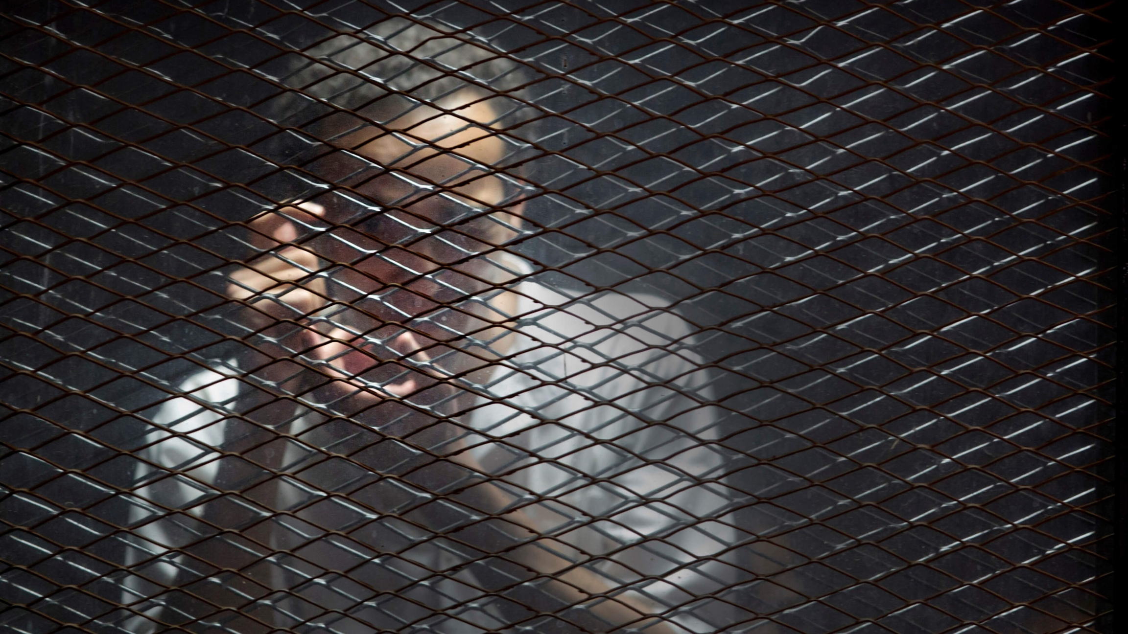 Egyptian photojournalist Mahmoud Abu Zied, known by his nickname Shawkan, gestures in a soundproof glass cage.