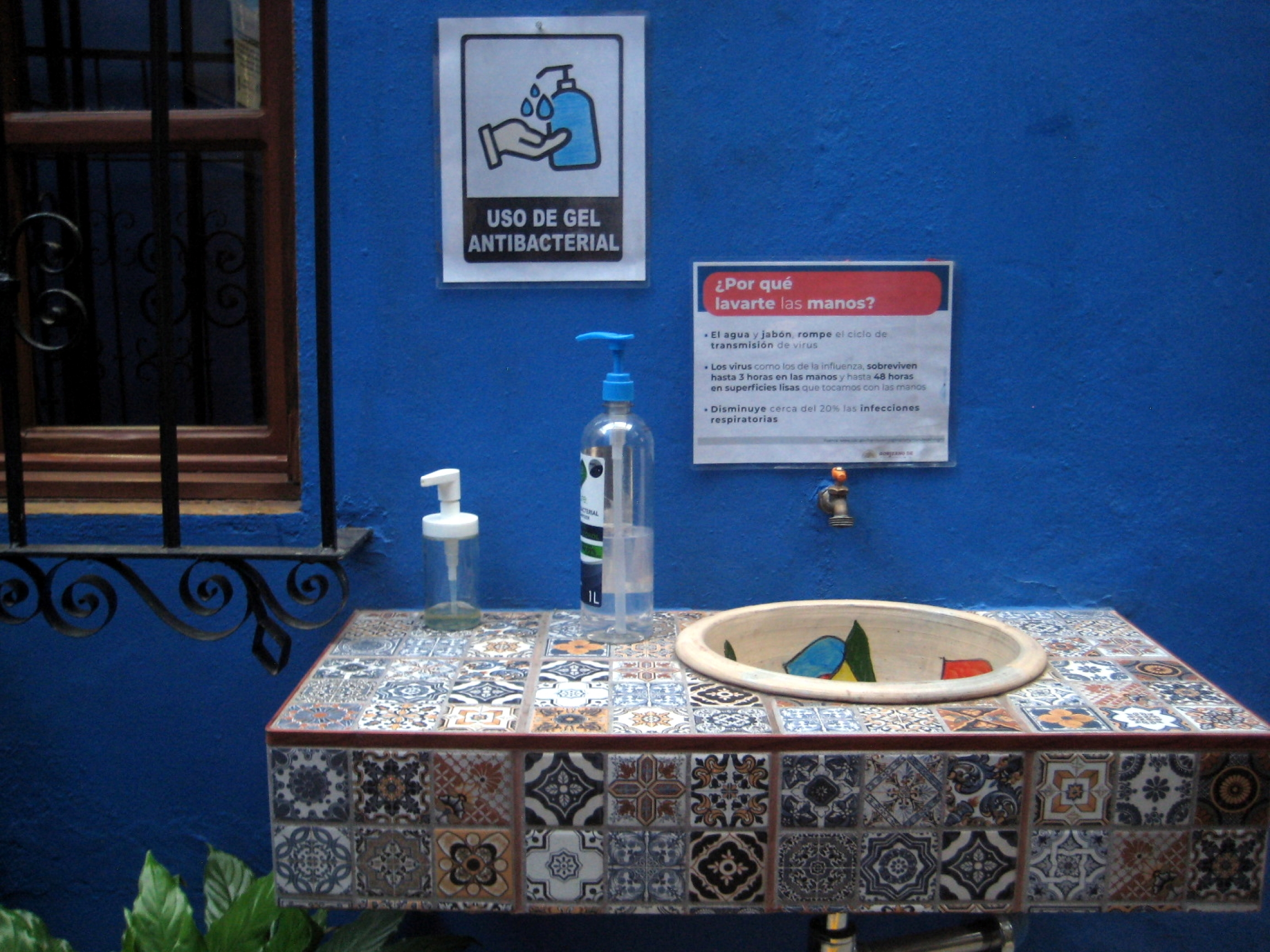 Hygiene station at the entrance of Las Golondrinas Hotel include a sink for hand-washing and a bottle with antibacterial gel.