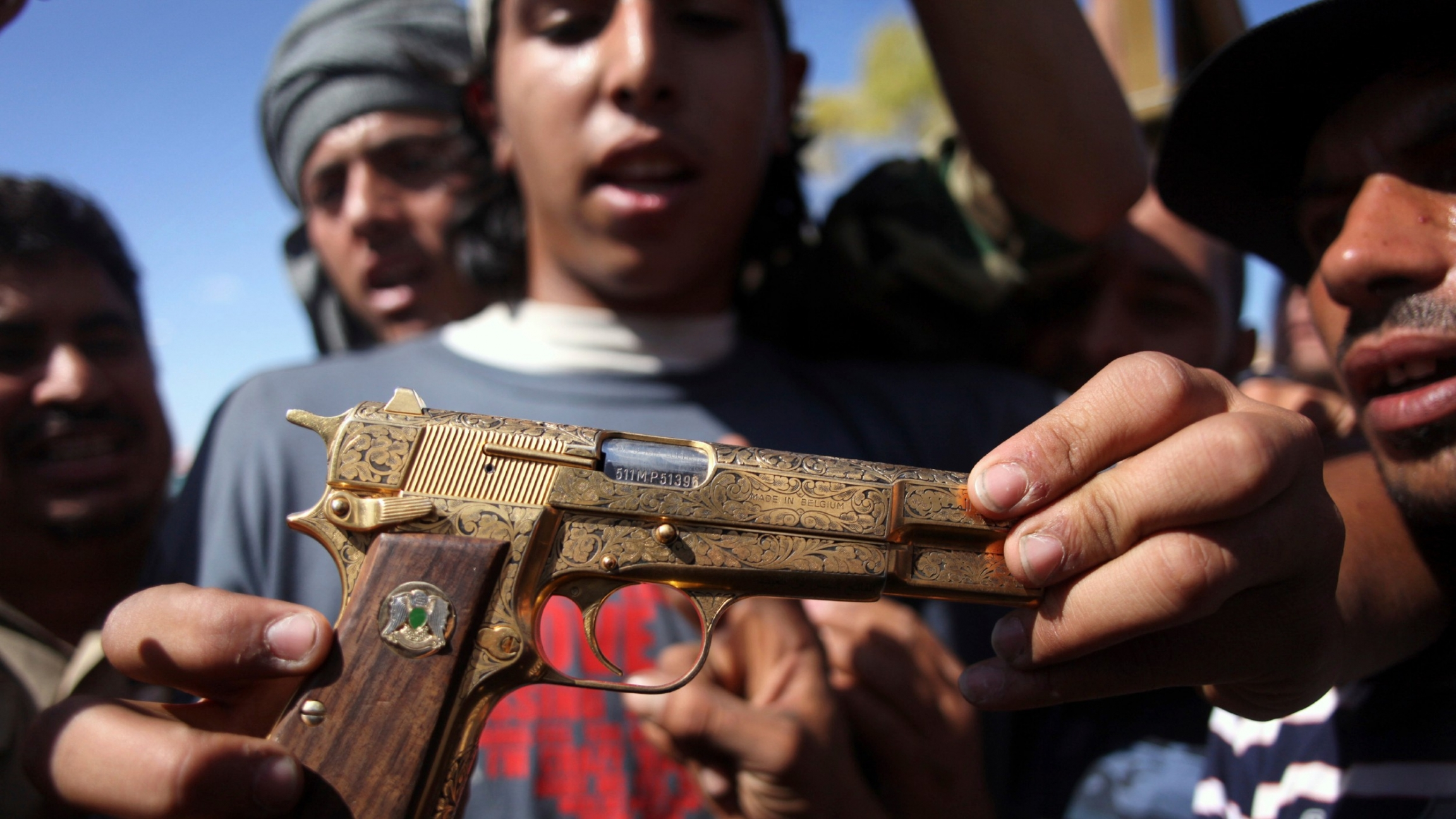 Mohammed al-Babi holds a golden pistol he says belonged to Muammar Gadhafi in Sirte, Libya.
