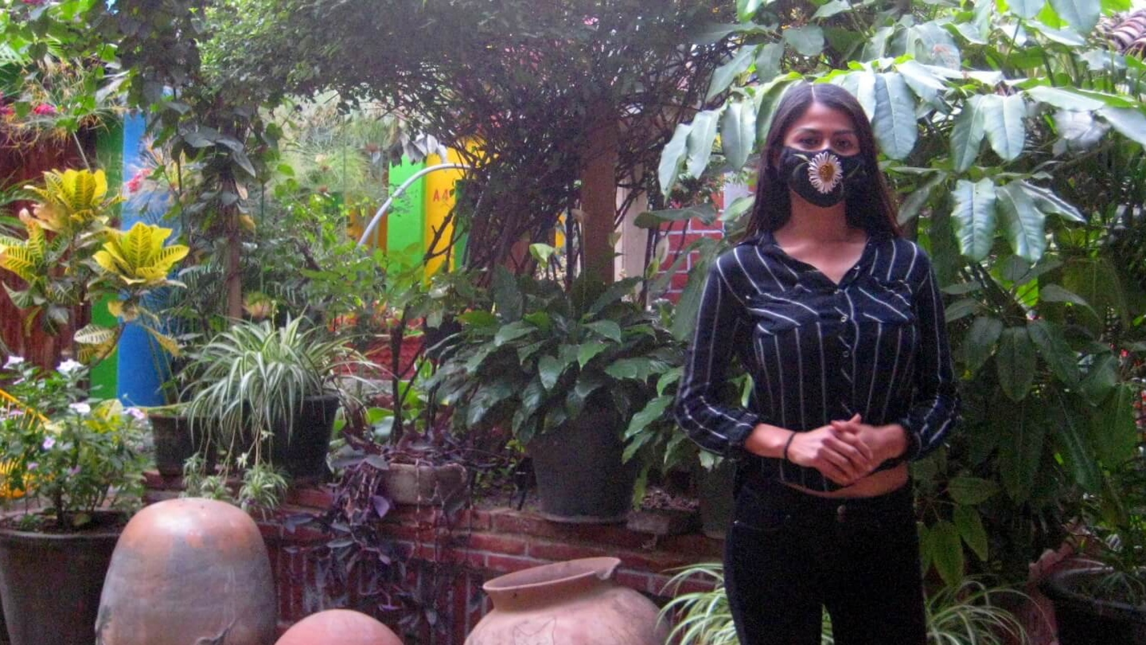 Sandra Martínez stands in a plant-filled patio of the Las Golondrinas Hotel.