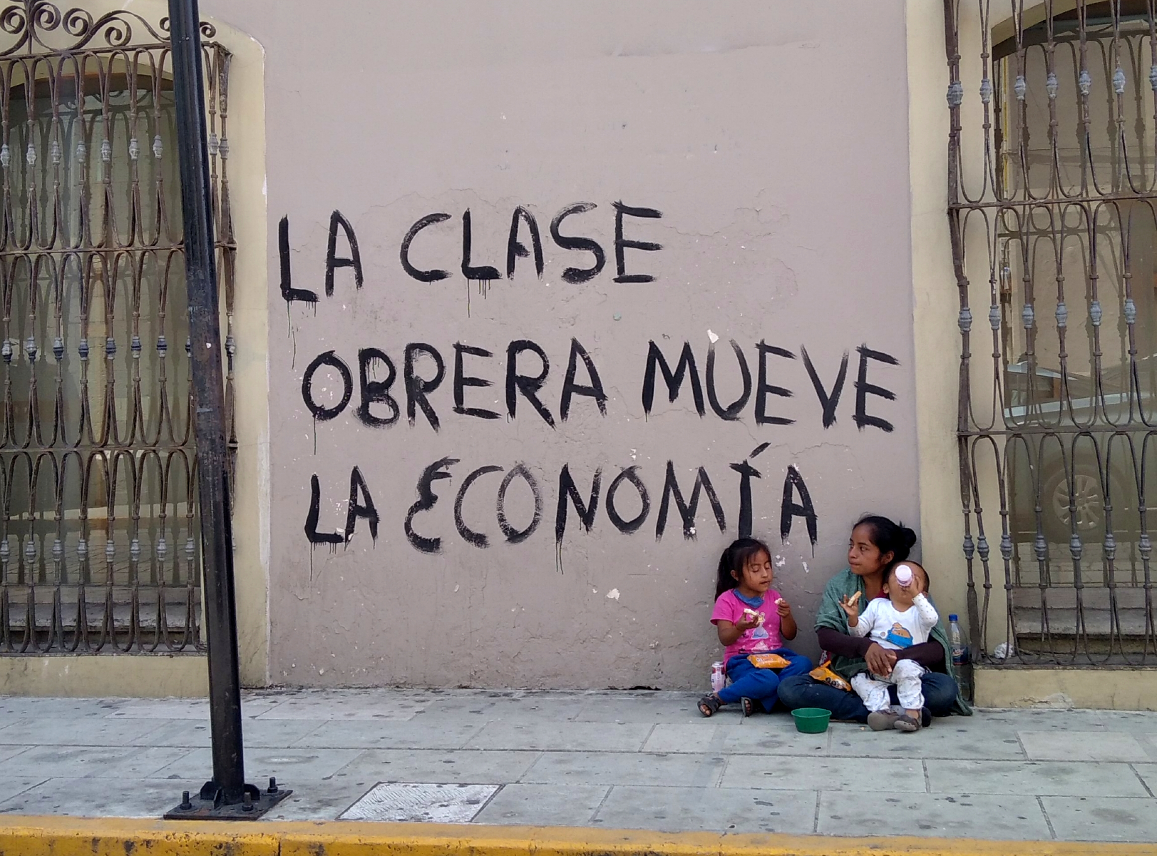 "A woman with children asks passersby in downtown Oaxaca for spare change next to a wall painted with a slogan that reads ""The working class moves the economy."""