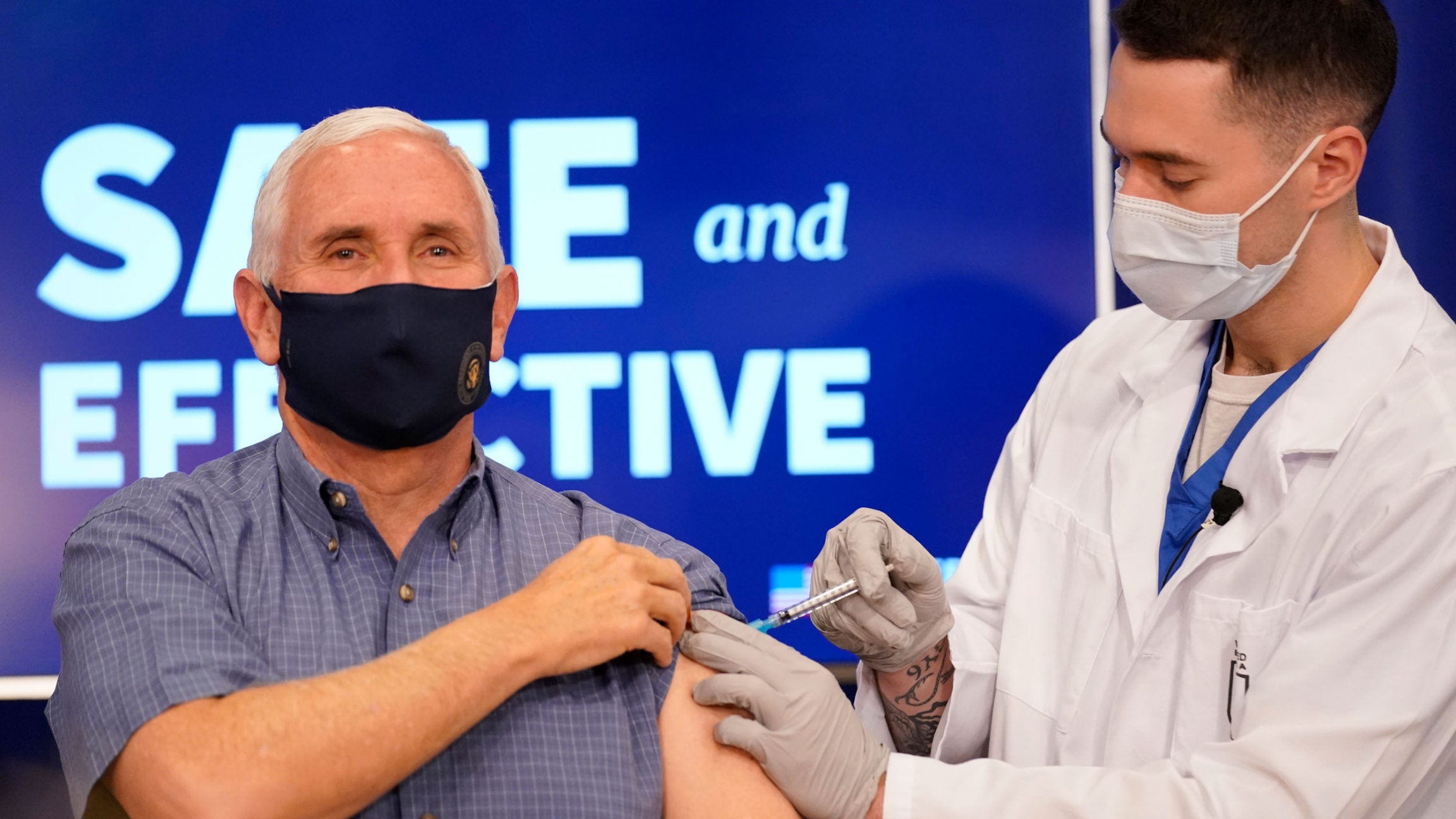US Vice President Mike Pence is shown holding his sleeve up while a doctor injects the Pfizer-BioNTech COVID-19 vaccine shot in his shoulder.