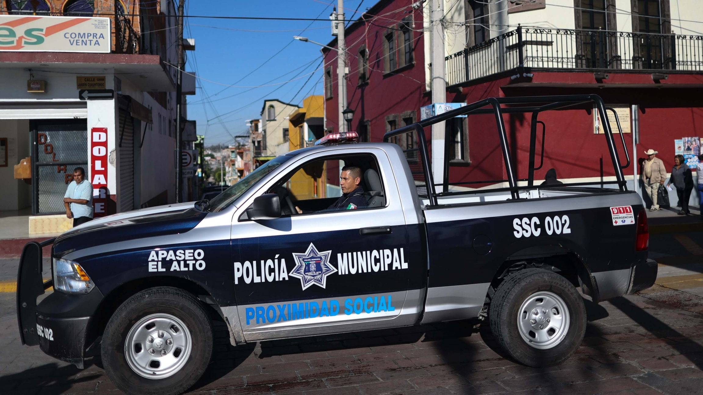 A police officer drives a large blue and white police vehicle through town
