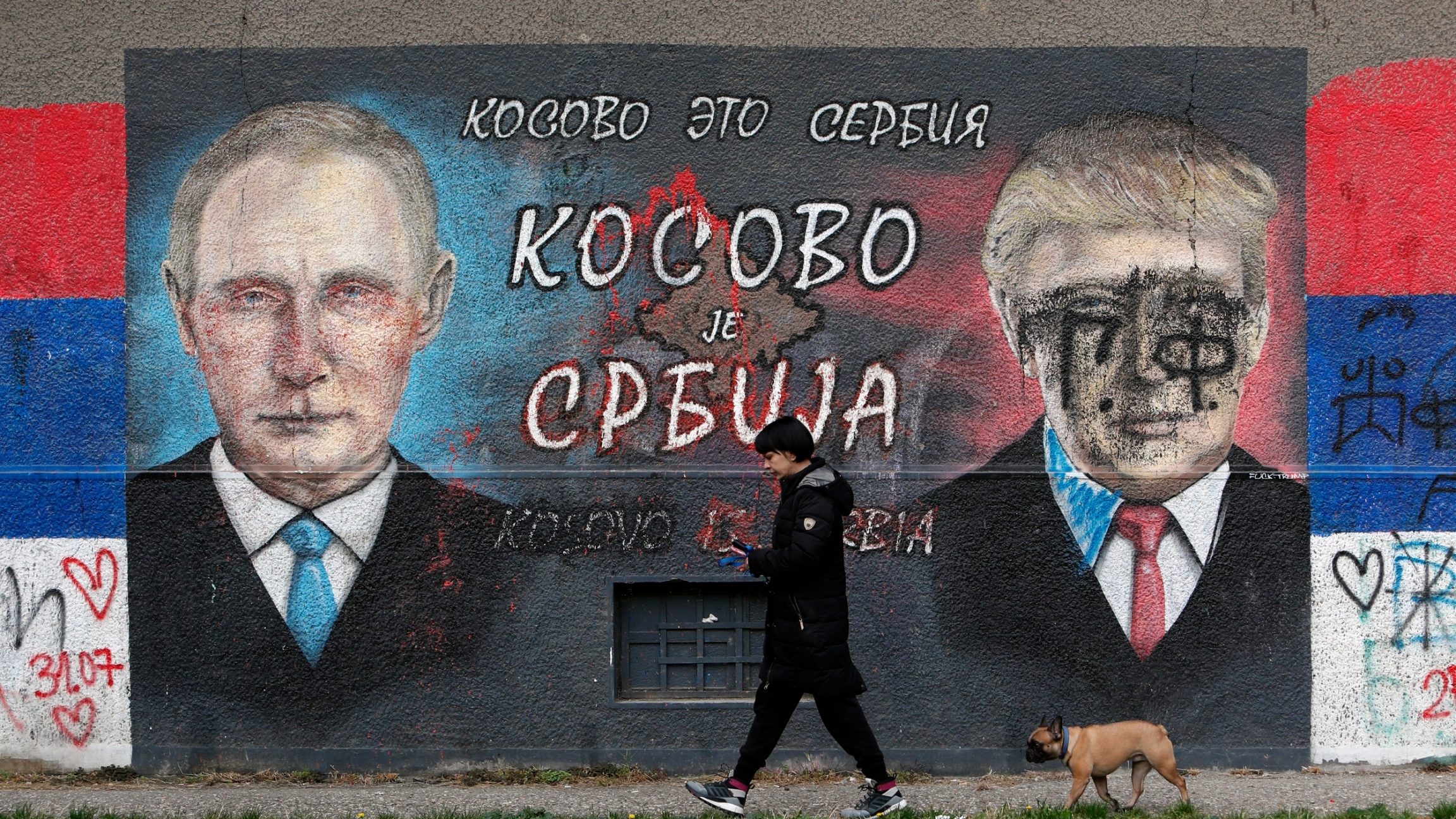 A woman with a dog passes by graffiti depicting the Russian President Vladimir Putin, left, and US President Donald Trump vandalized with paint in a suburb of Belgrade, Serbia, Nov. 3, 2020.