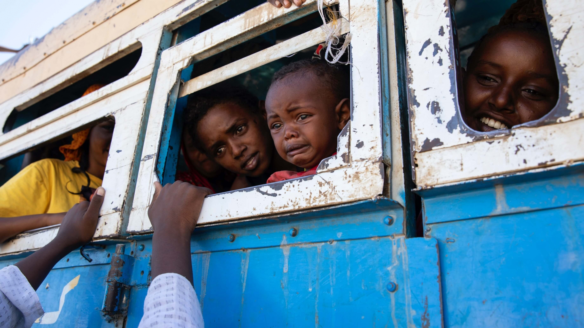 Three Ethiopian travelers sit inside a blue bus with white-bordered windows, saying goodbye to someone whose arms rest on the window frame.