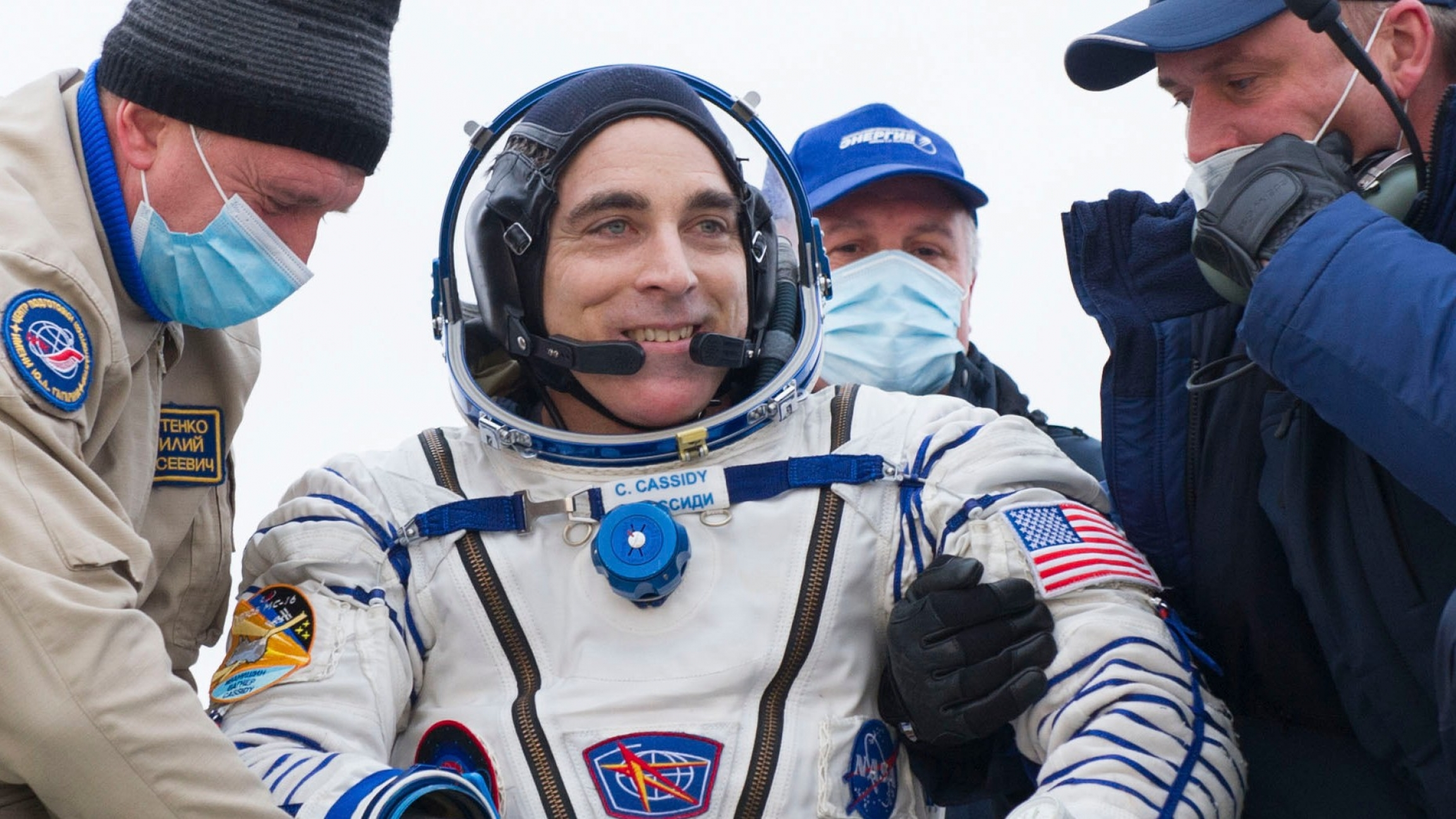 In this handout photo released by Gagarin Cosmonaut Training Centre (GCTC) and theRoscosmos space agency, NASA astronaut Chris Cassidy, center, reactsafter landing near the town of Dzhezkazgan, Kazakhstan, Oct. 22, 2020.