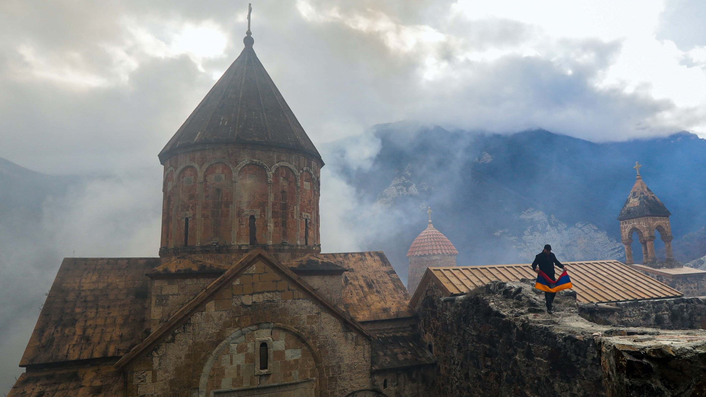 A man with an Armenian national flag visits a 12th-13th an old brick monastery surrounded by mountain vistas