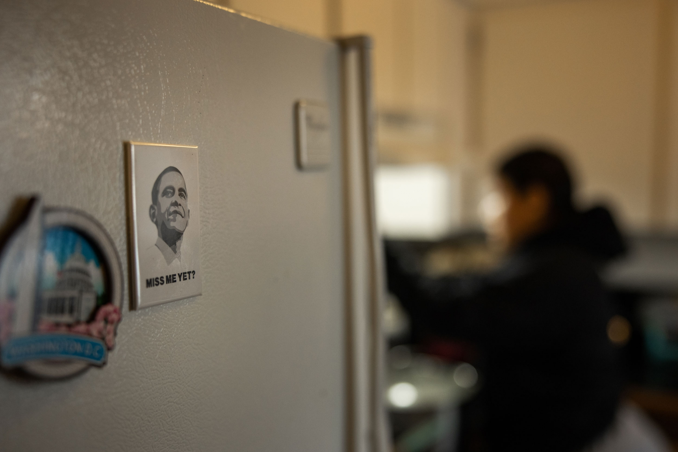 A magnet with a portrait of President Barack Obama is shown with a woman in the distance in soft focus.