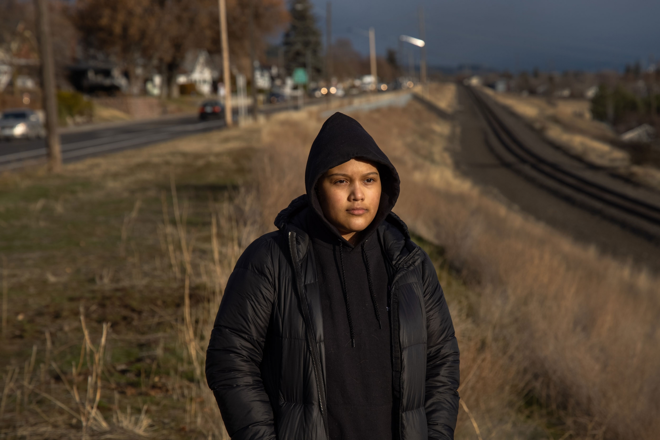 A woman is shown wearing a dark hooded sweatshirt and jacket while standing near a set of railroad tracks.