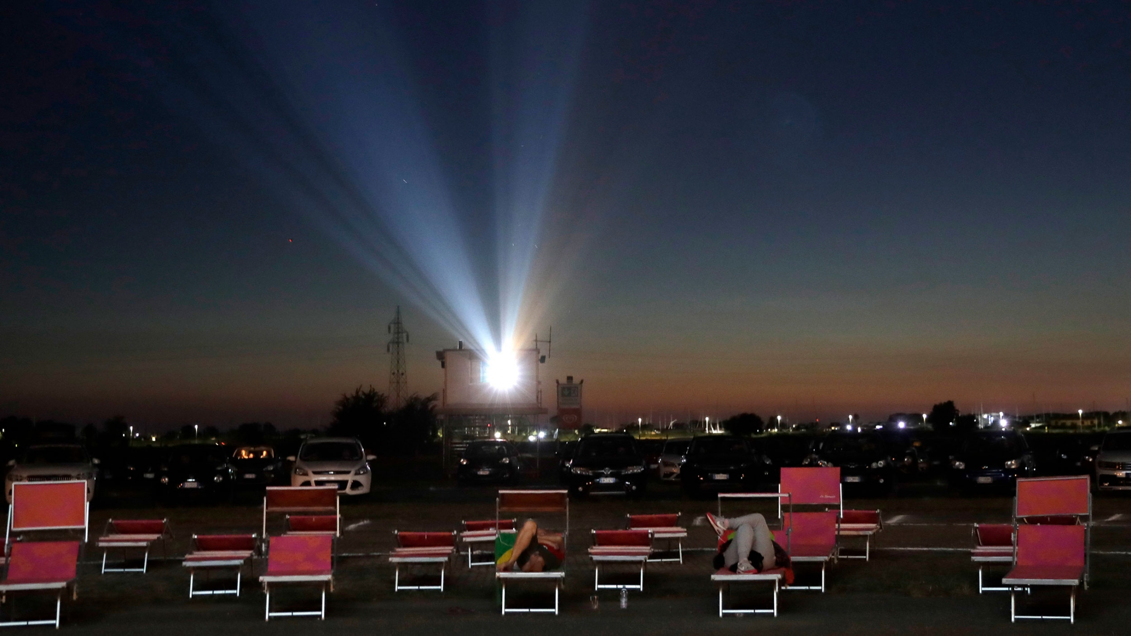 Several rows of outdoor seating are shown with cars in the distance and a movie project shining bright in the distance.
