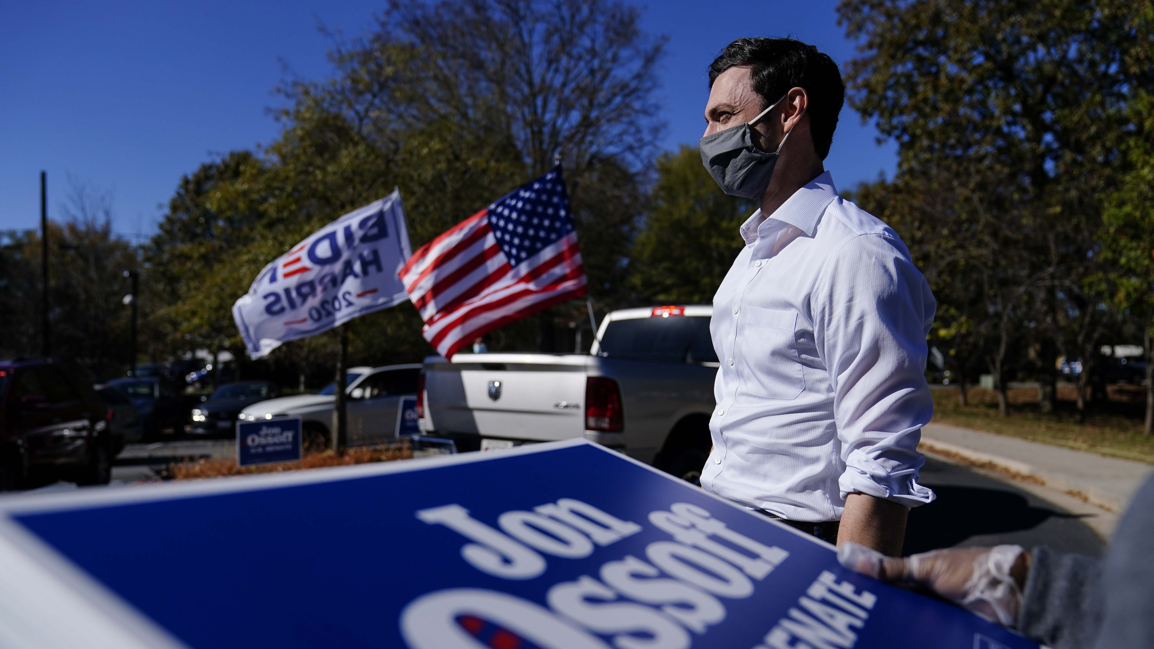 Georgia Democratic candidate for US Senate Jon Ossoff waits for a supporter to arrive during a drive-through yard sign pick-up event on Nov. 18, 2020, in Marietta, Georgia.