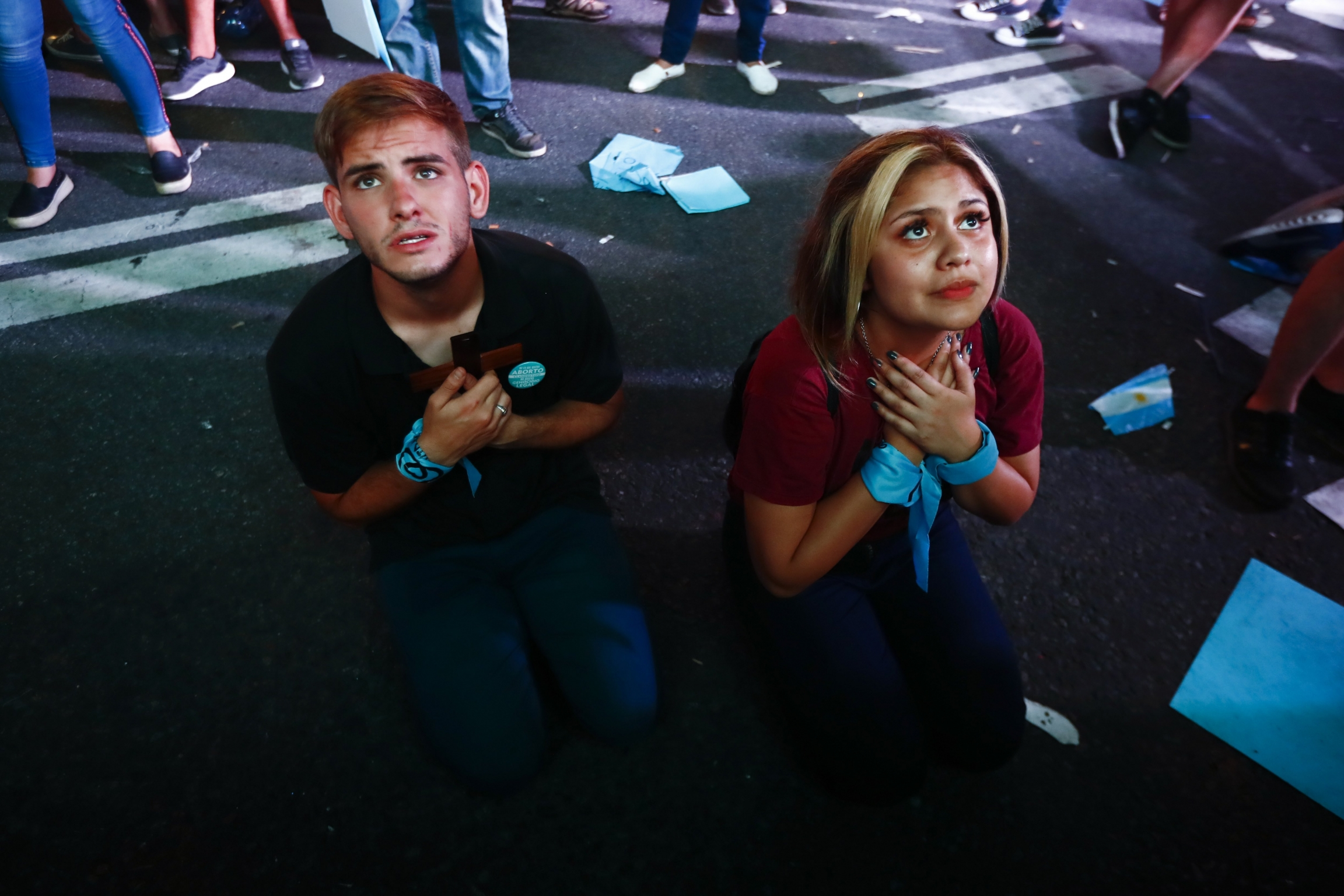 A young man and a young woman, wearing a blue scarf around their wrist, kneel down to pray on the street.