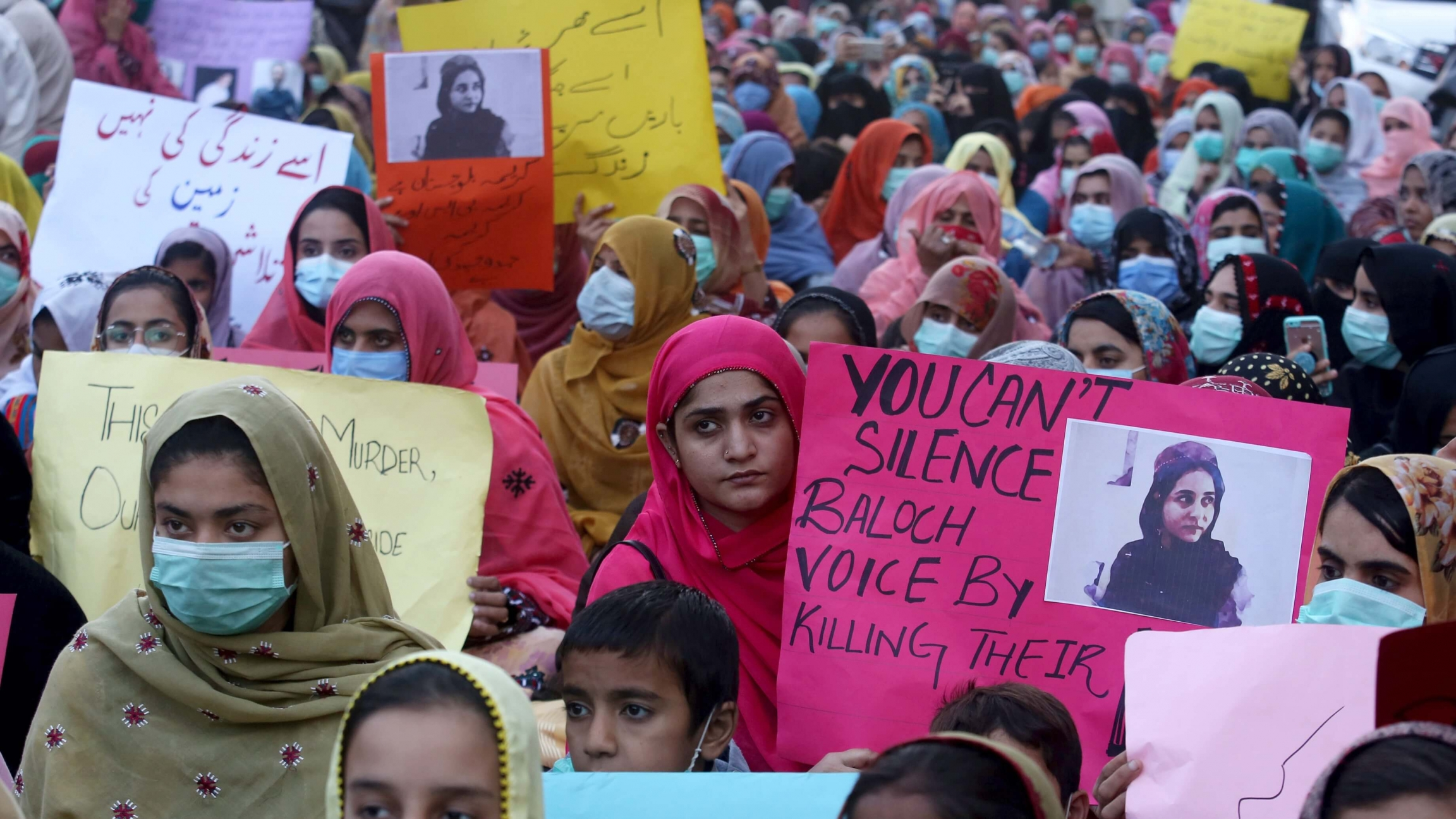 A massive protest of women wearing colorful head wraps and masks with signs supporting Karima Mehrab Baloch.