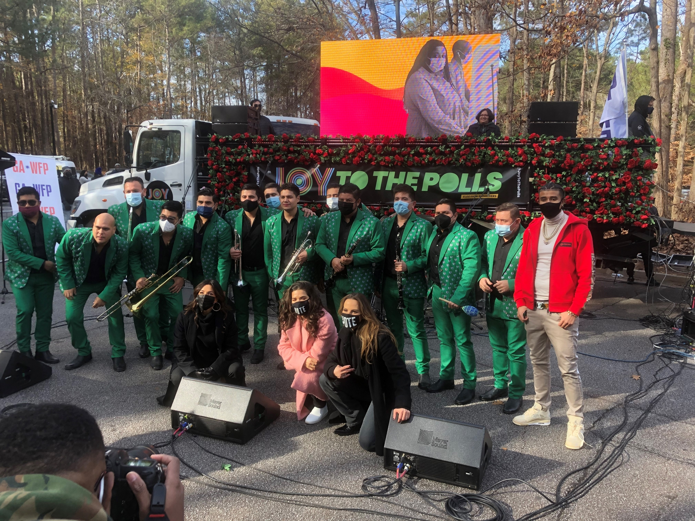 A group of musicians wearing green uniforms and other actors and musicians stand outside together.
