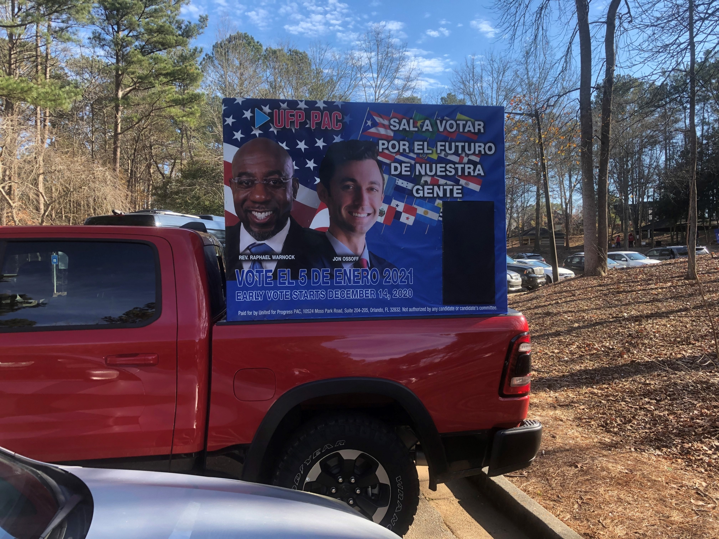 A red campaign truck features candidates Rev. Raphael Warnock and Jon Ossoff.