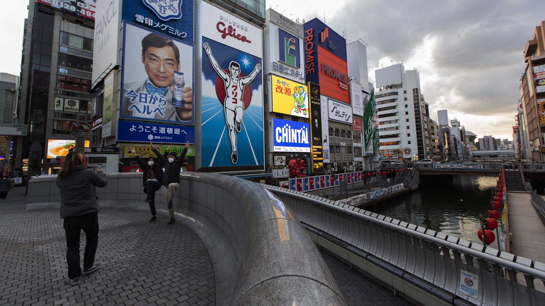 People pose for a photo, mimicking the character in an advertisement as they visit Ebisu-bashi bridge, a popular tourist spot in Osaka, western Japan, Nov. 30, 2020.