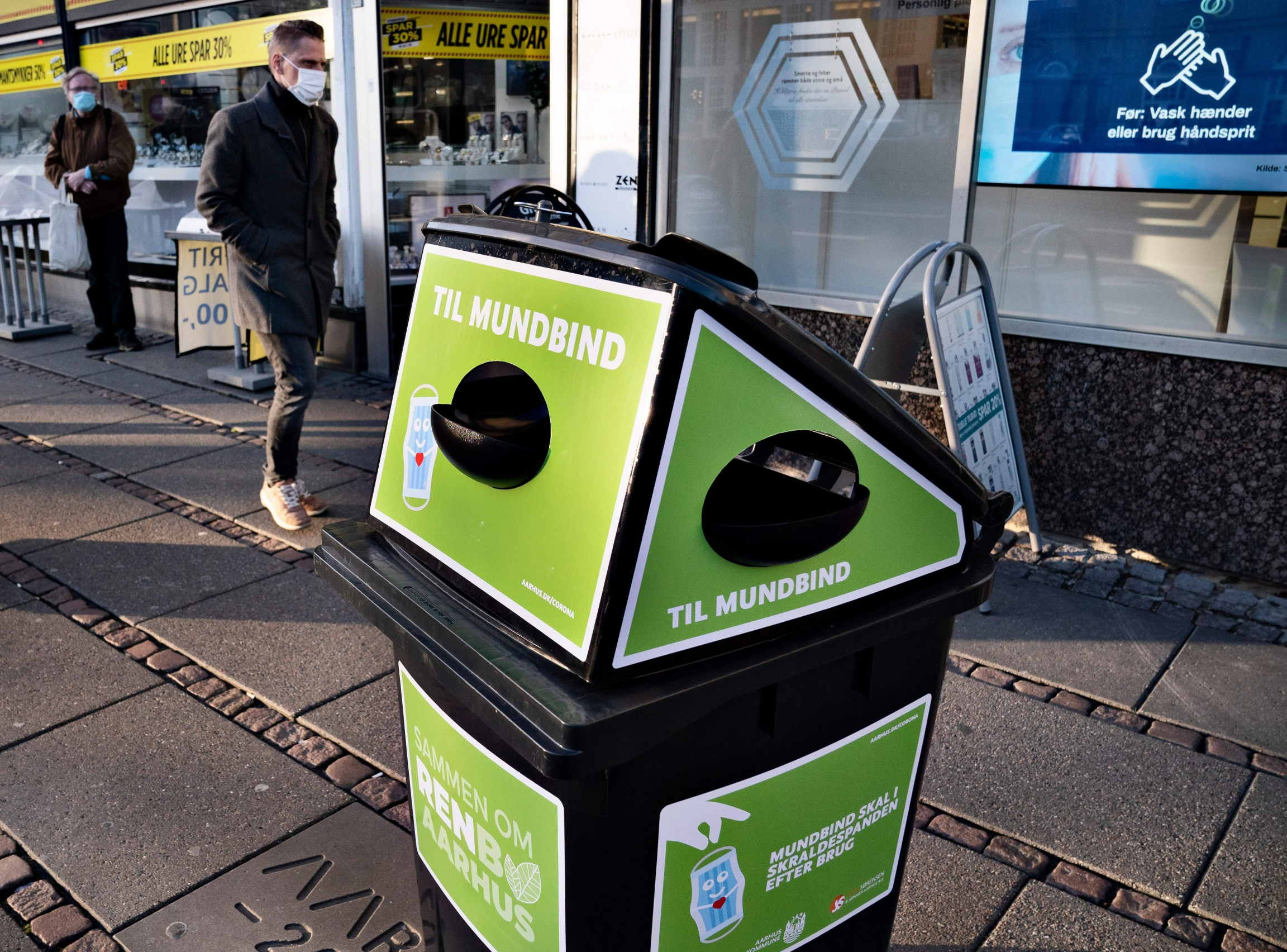 A green trash bin on a sidewalk in Denmark.
